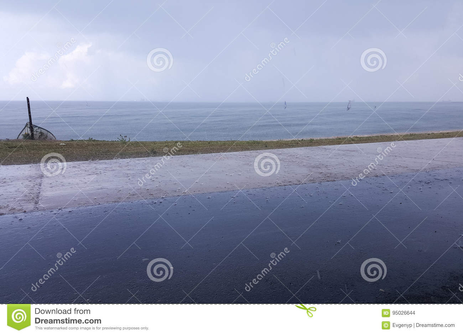 El tiempo nublado en la costa, personas que practica surf monta en la lluvia, colgando se nubla