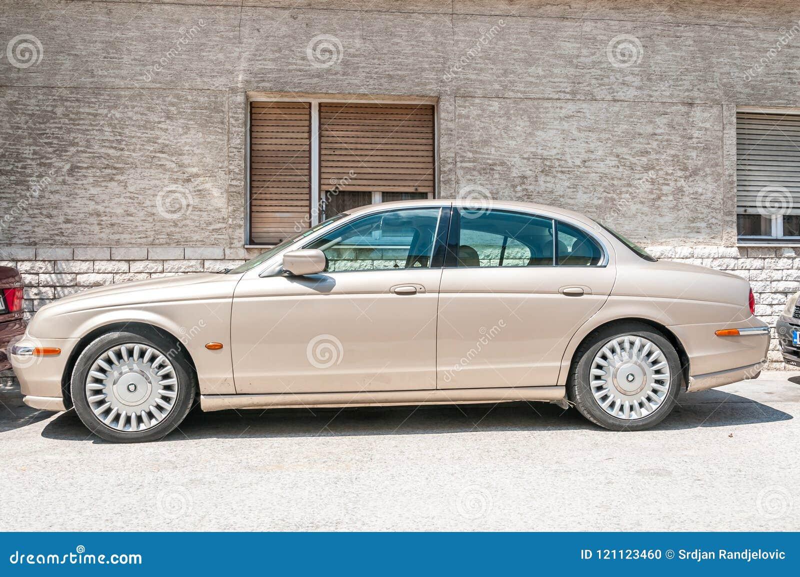 El tipo coche clásico de Jaguar S del salón de V6 parqueó en la calle