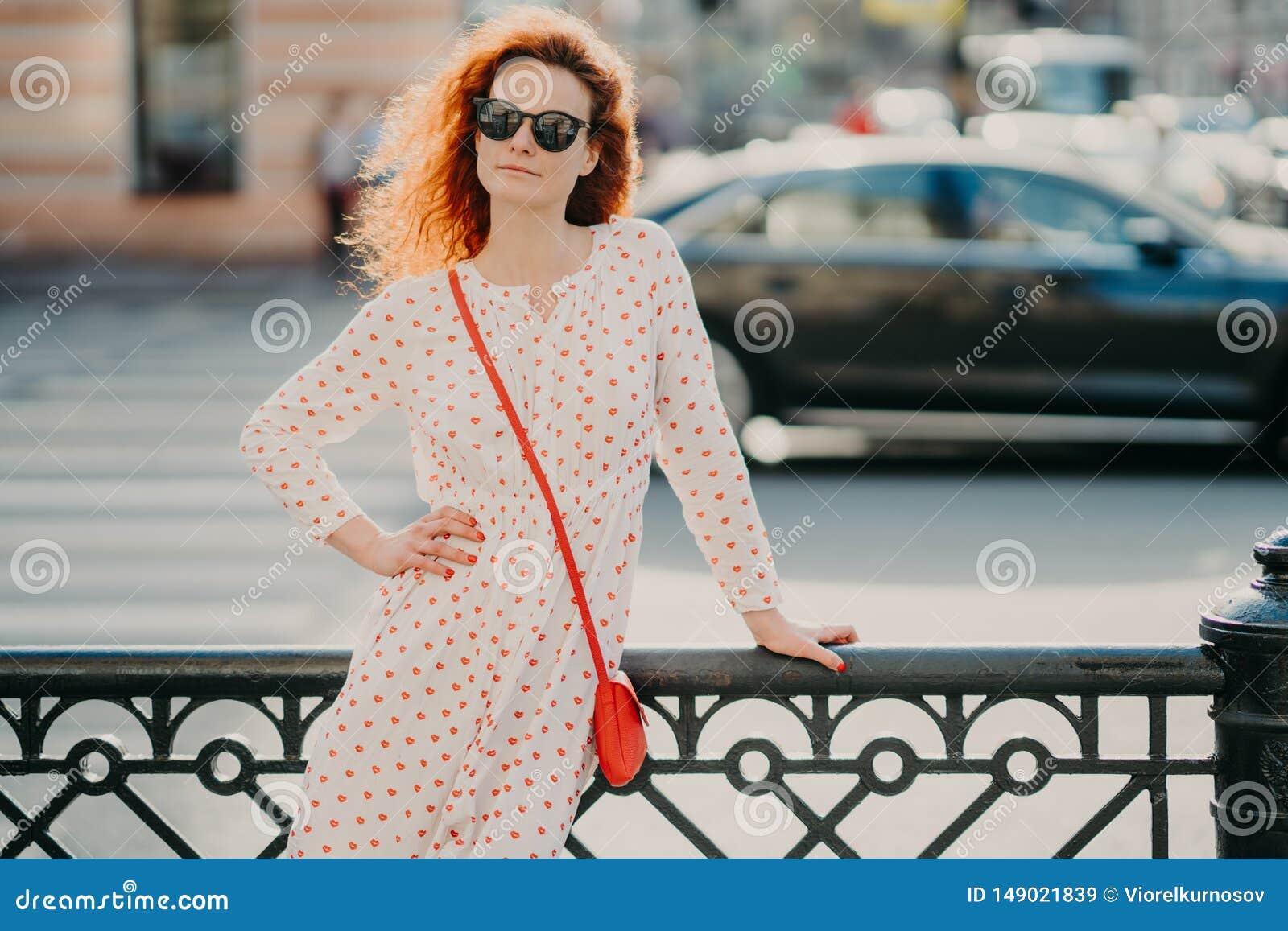 El tiro al aire libre de la mujer satisfecha del pelirrojo guarda una mano en la cintura, otra en la calle por lo tanto, las acti