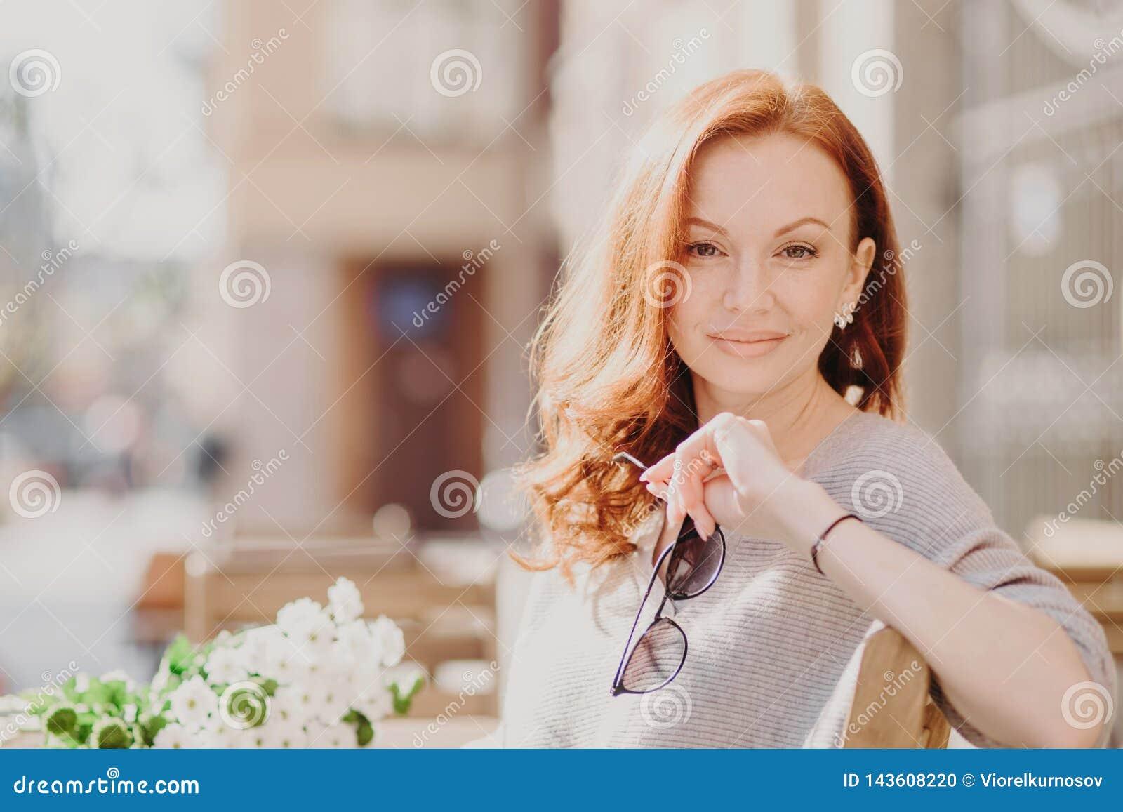 El tiro horizontal de la mujer pelirroja contenta atractiva se sienta en banco, disfruta de día soleado, sostiene las gafas de so