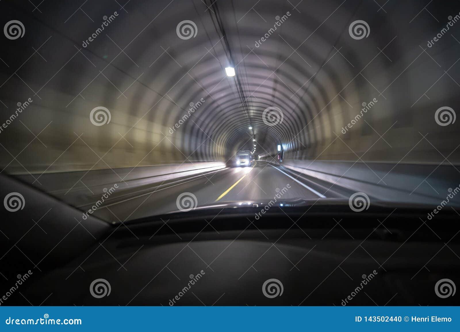El tiro largo de la exposición del túnel en Lofoten por dentro de un coche que esté moviendo tan la luz crea efecto de la visión