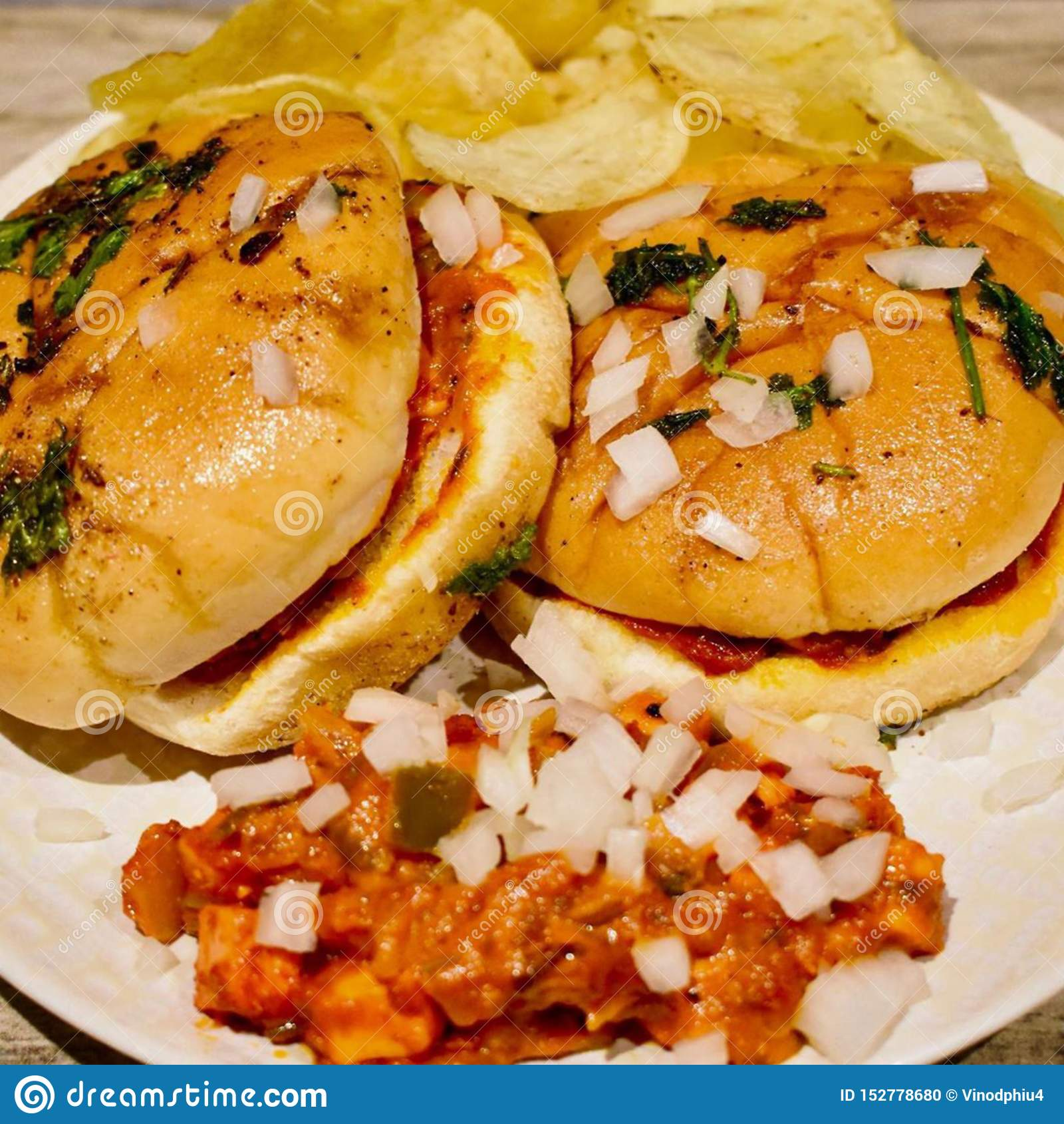 El tomate del burgerA de Tawa basó el curry vegetal mezclado con queso y el panner mezclado a través, extensión sobre pedazos de