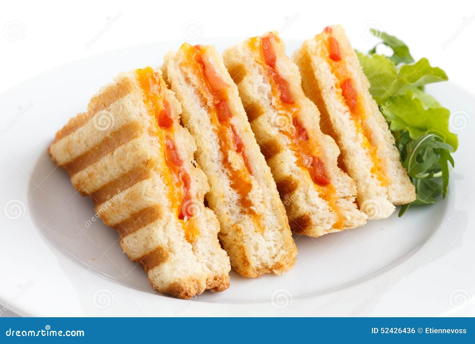 El tomate y el queso clásicos tostaron el bocadillo en la placa blanca