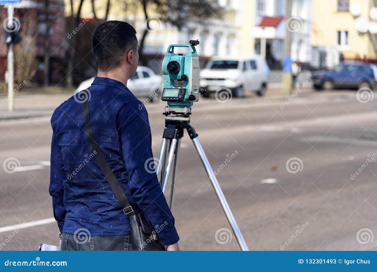 El topógrafo de la tierra del ingeniero hace medidas en la calle de la ciudad de Chernigov, Ucrania