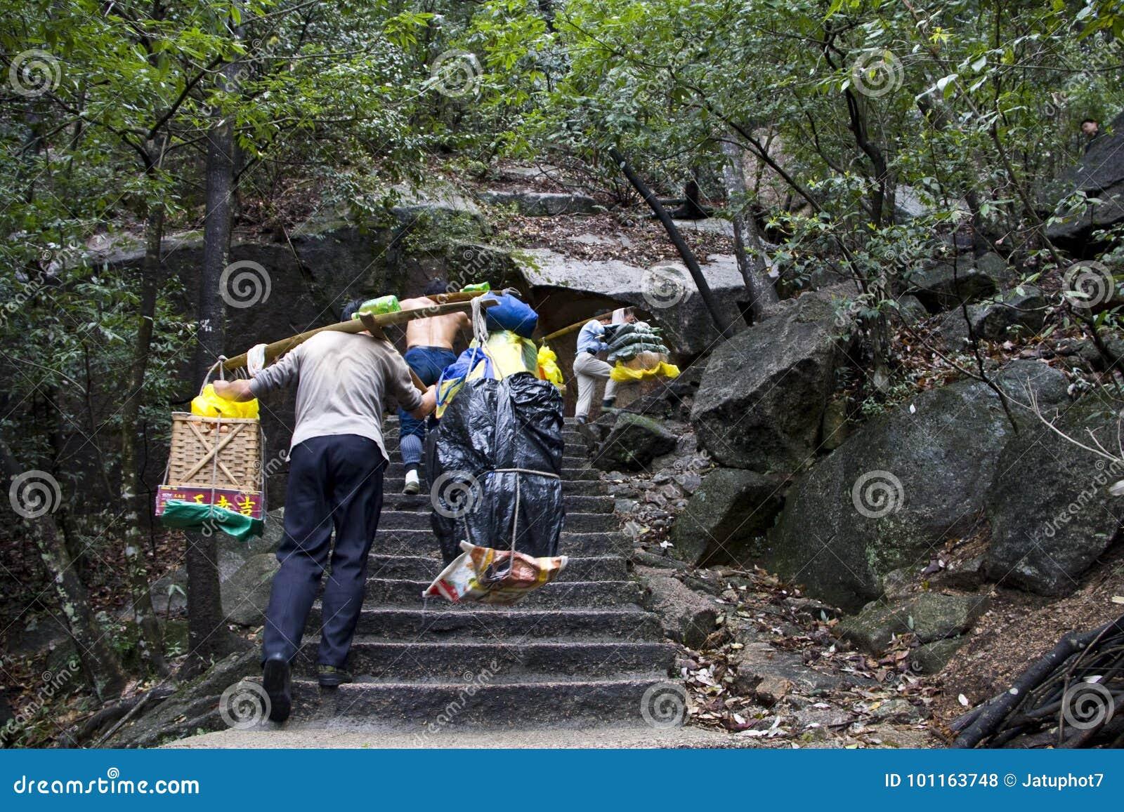 El trabajador chino del hombre, lleva toda la materia a la montaña Huangshan