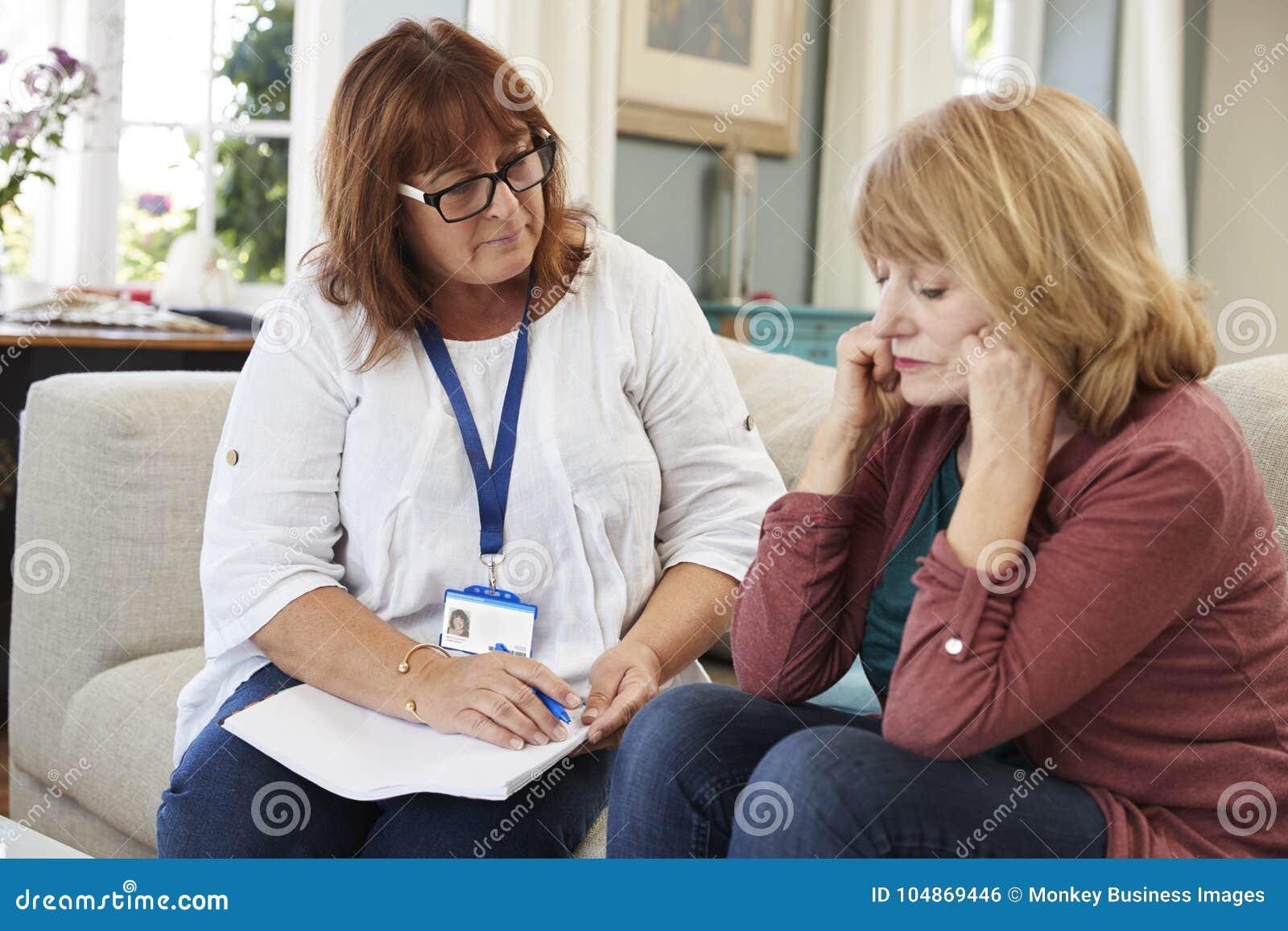 El trabajador de la ayuda visita a la mujer mayor que sufre con la depresión