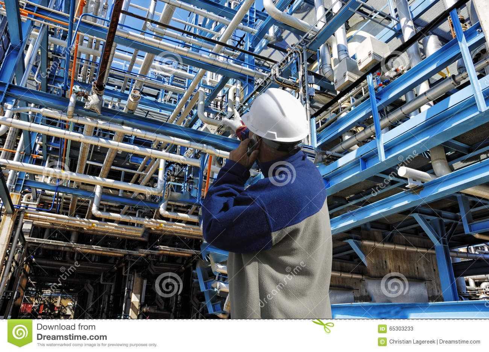 El trabajador de la refinería dentro del gigante canaliza construcciones