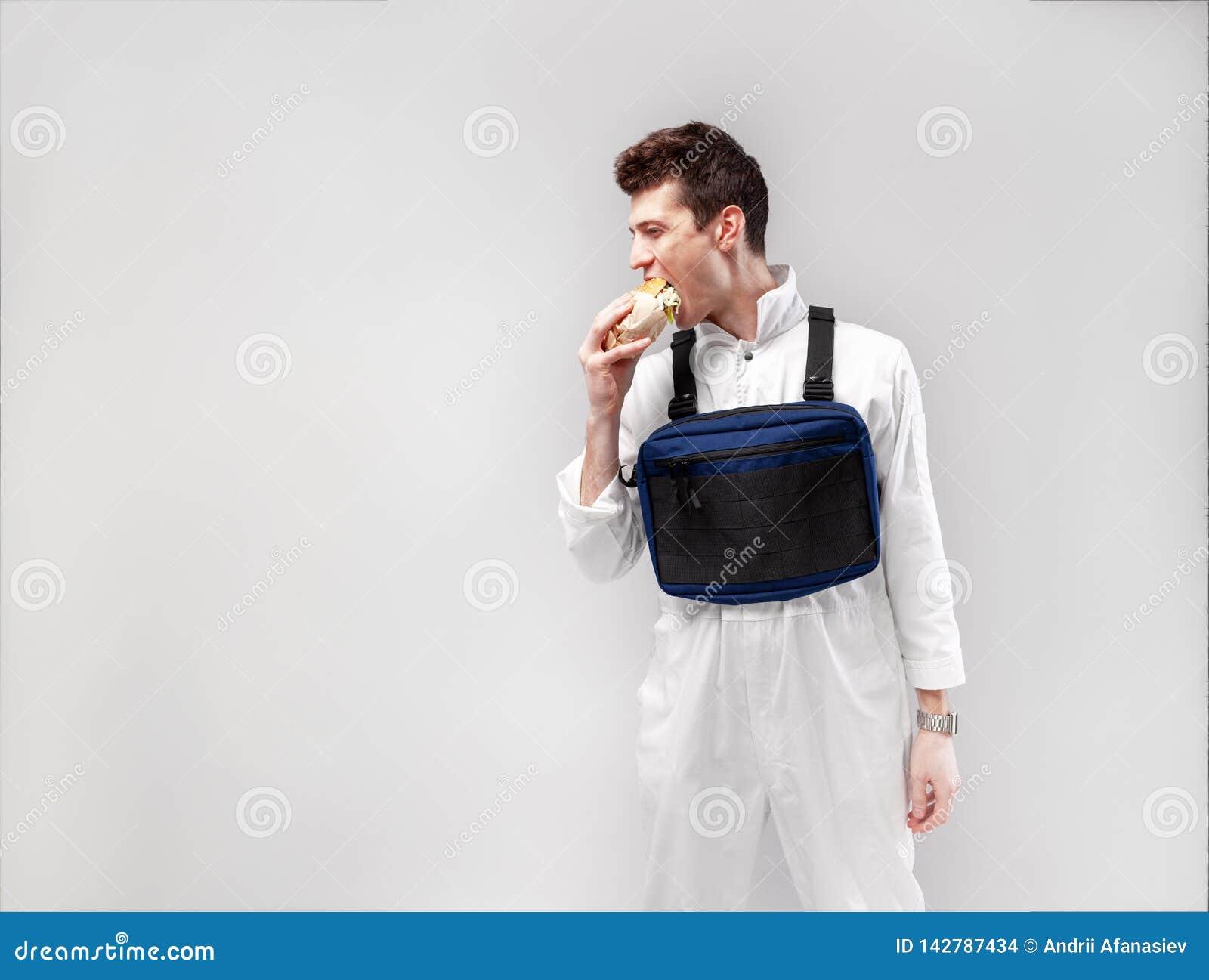 El trabajador de sexo masculino elegante joven con el bolso del aparejo del pecho está comiendo una hamburguesa jugosa sabrosa en