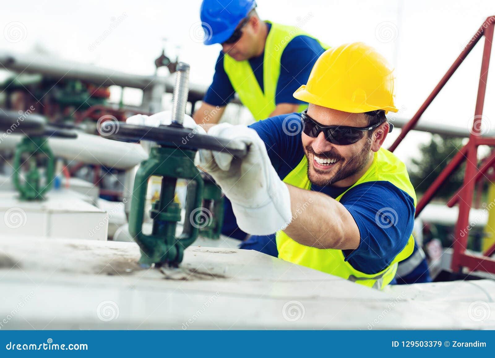El trabajador del aceite cierra la válvula en el oleoducto