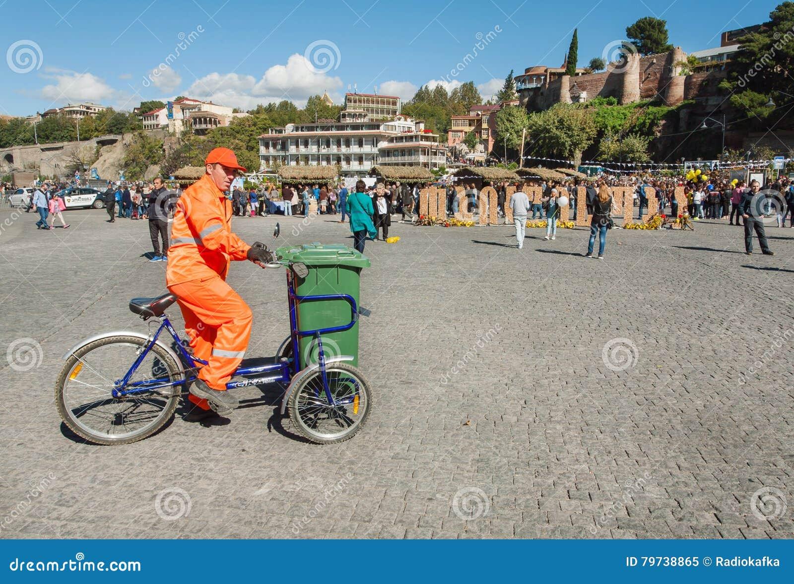 El trabajador del servicio de la ciudad en uniforme limpia la calle de la basura en una bicicleta