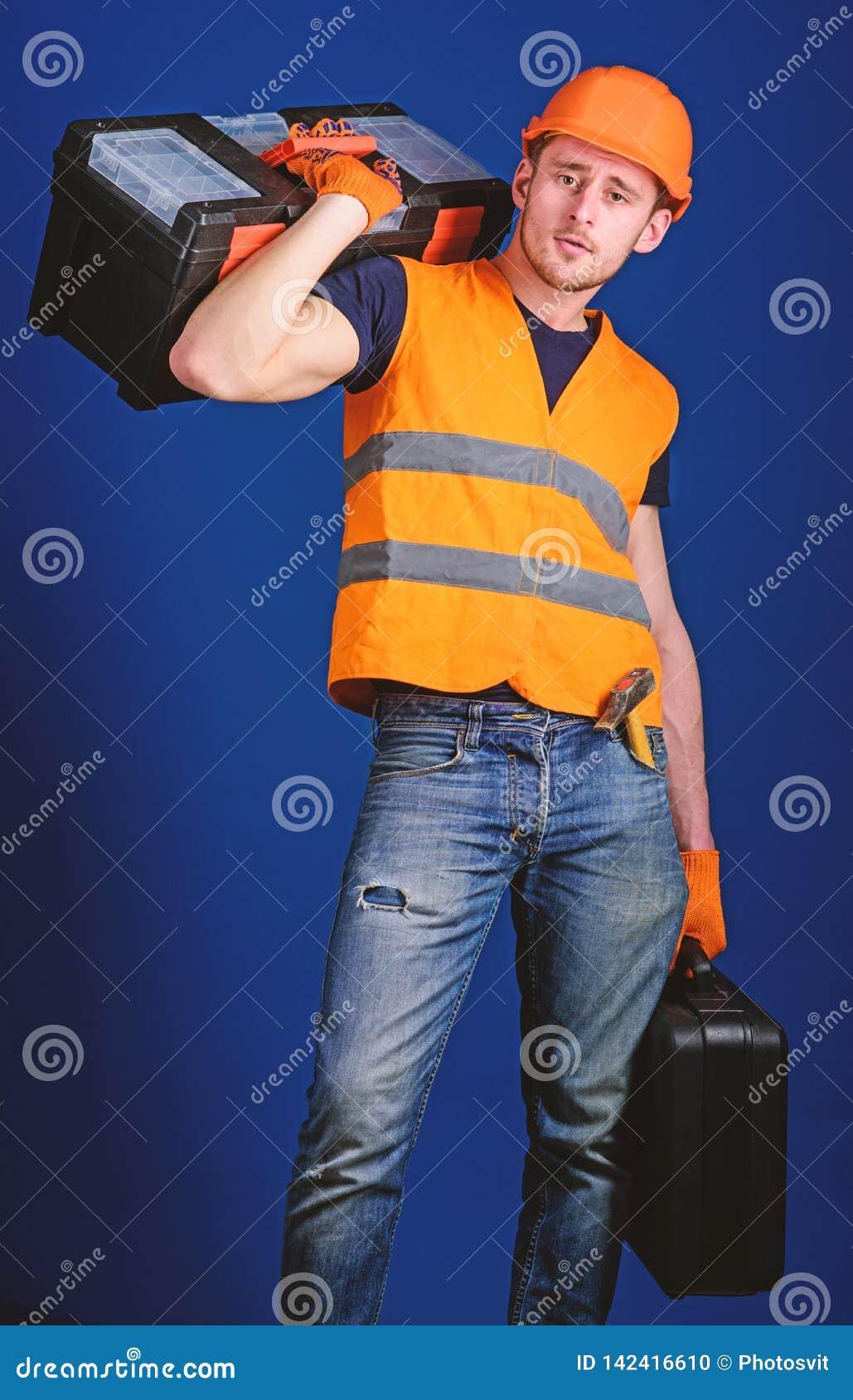 El trabajador, reparador, reparador, constructor en cara tranquila lleva la caja de herramientas en hombro, alista para trabajar