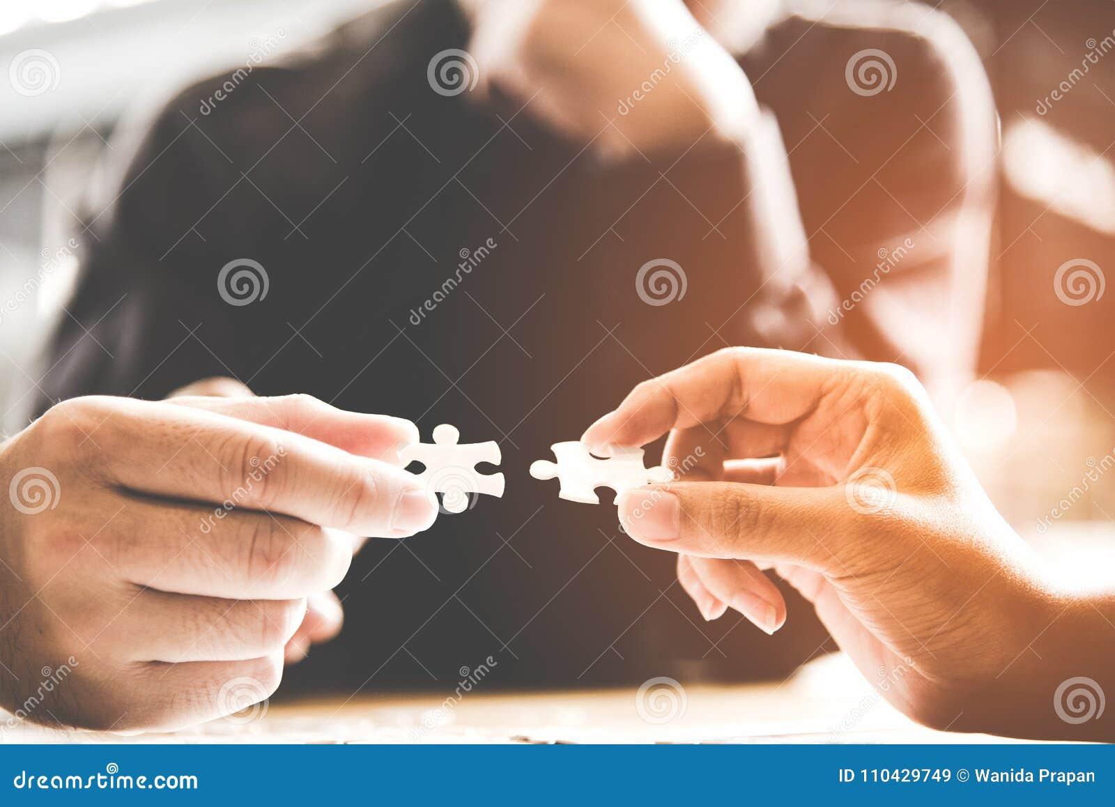 El trabajo del equipo del hombre de negocios que celebra dos pares de conexión del rompecabezas desconcierta el pedazo para hacer
