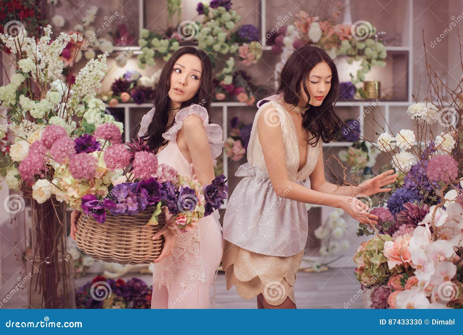 El trabajo feliz de los floristas asiáticos hermosos de las mujeres en tienda de flor con mucha primavera florece