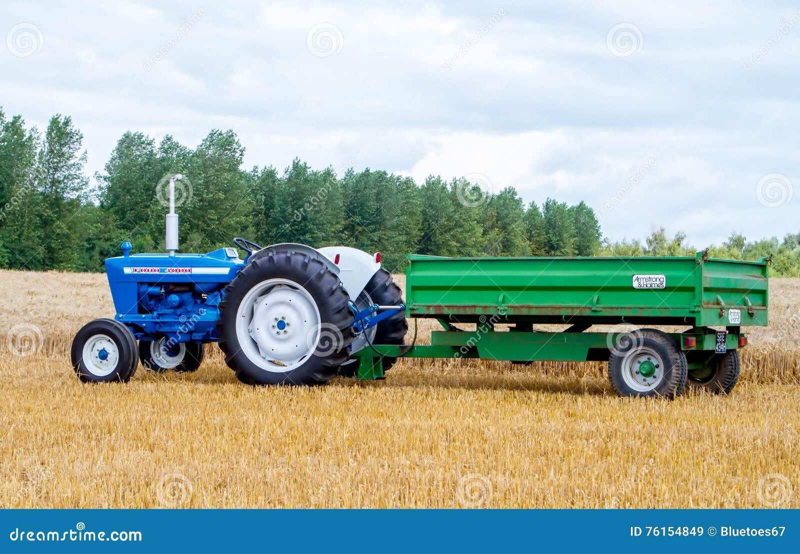 El tractor y el remolque viejos del vado 4000 del vintage en cosecha colocan