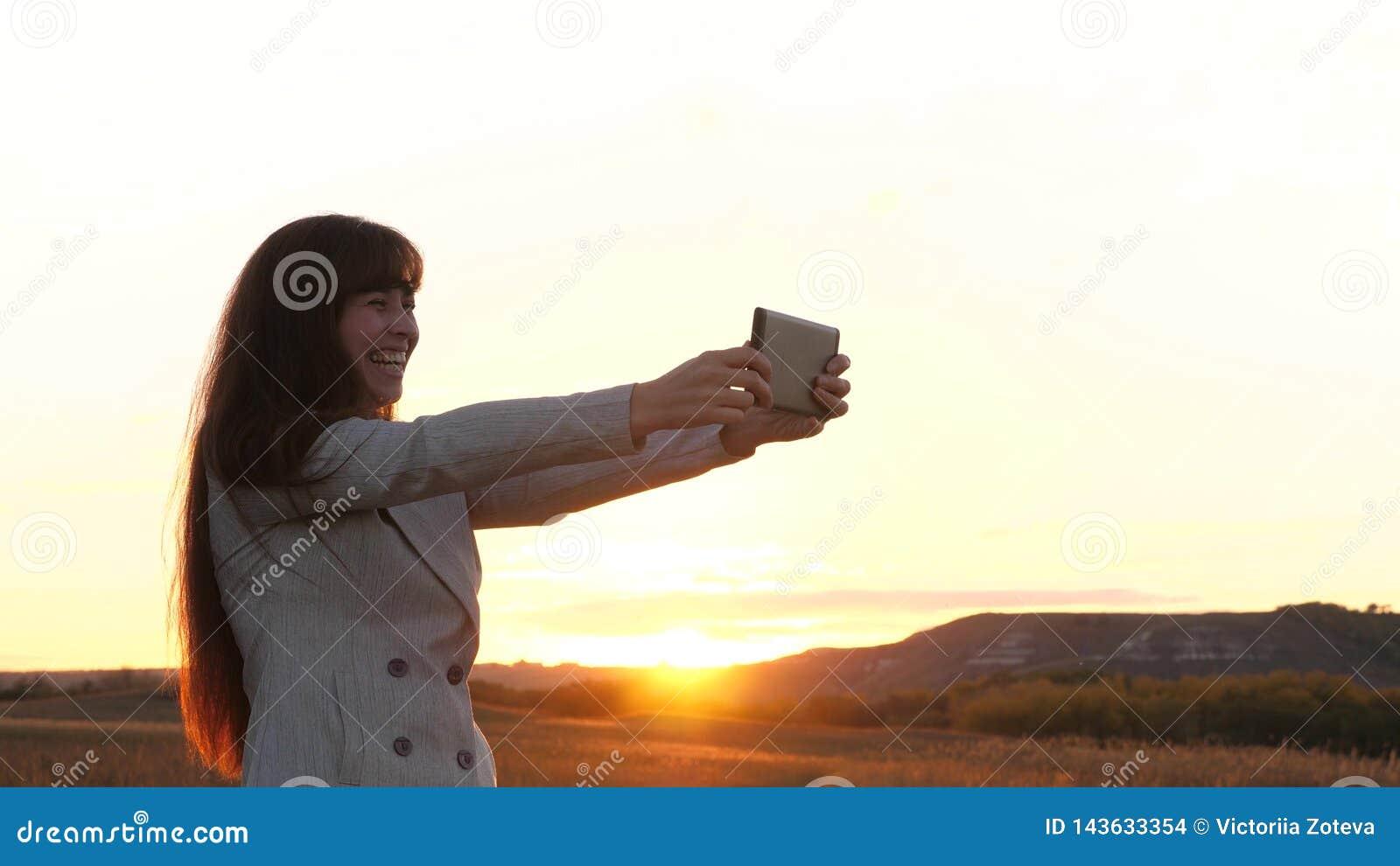 El turista de la muchacha en el campo hace el selfie con la tableta la mujer de negocios hermosa viaja y toma una foto del selfie