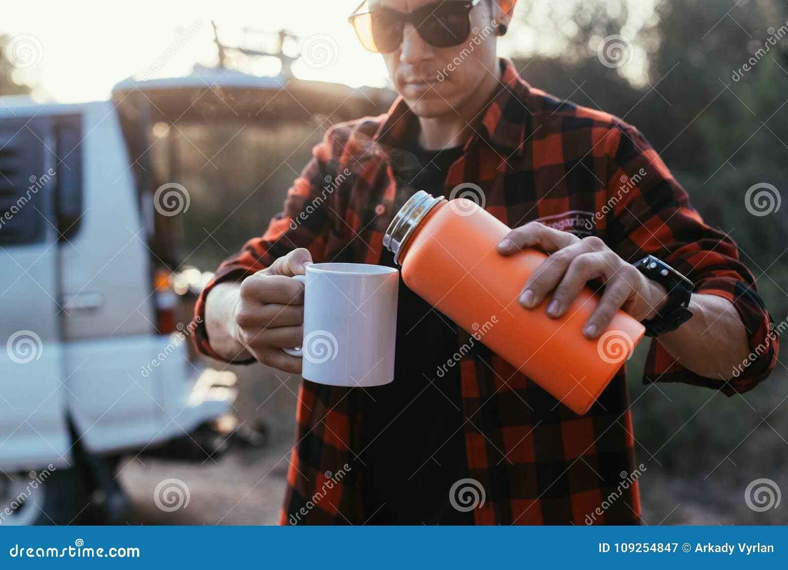El turista del aventurero vierte el café del termo
