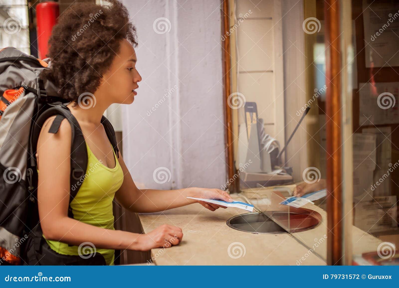 El turista femenino del backpacker compra un boleto en el tic de la estación terminal