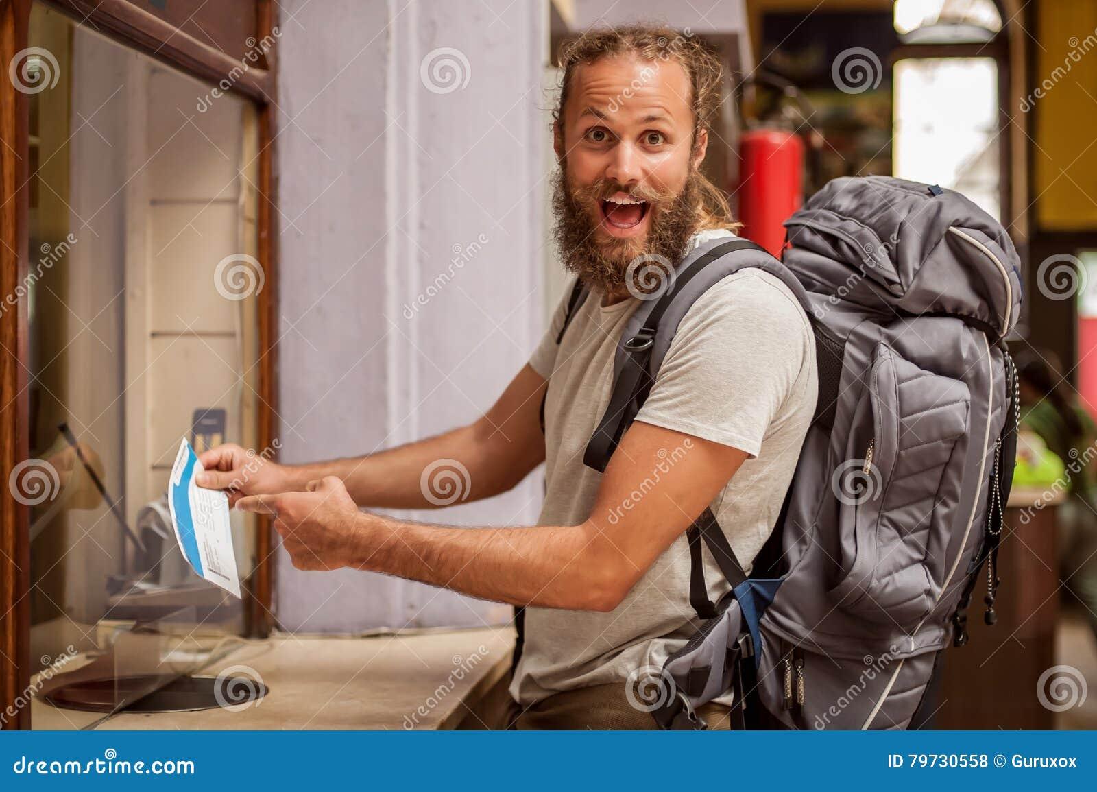 El turista masculino del backpacker feliz y eufórico muestra el boleto para el suyo