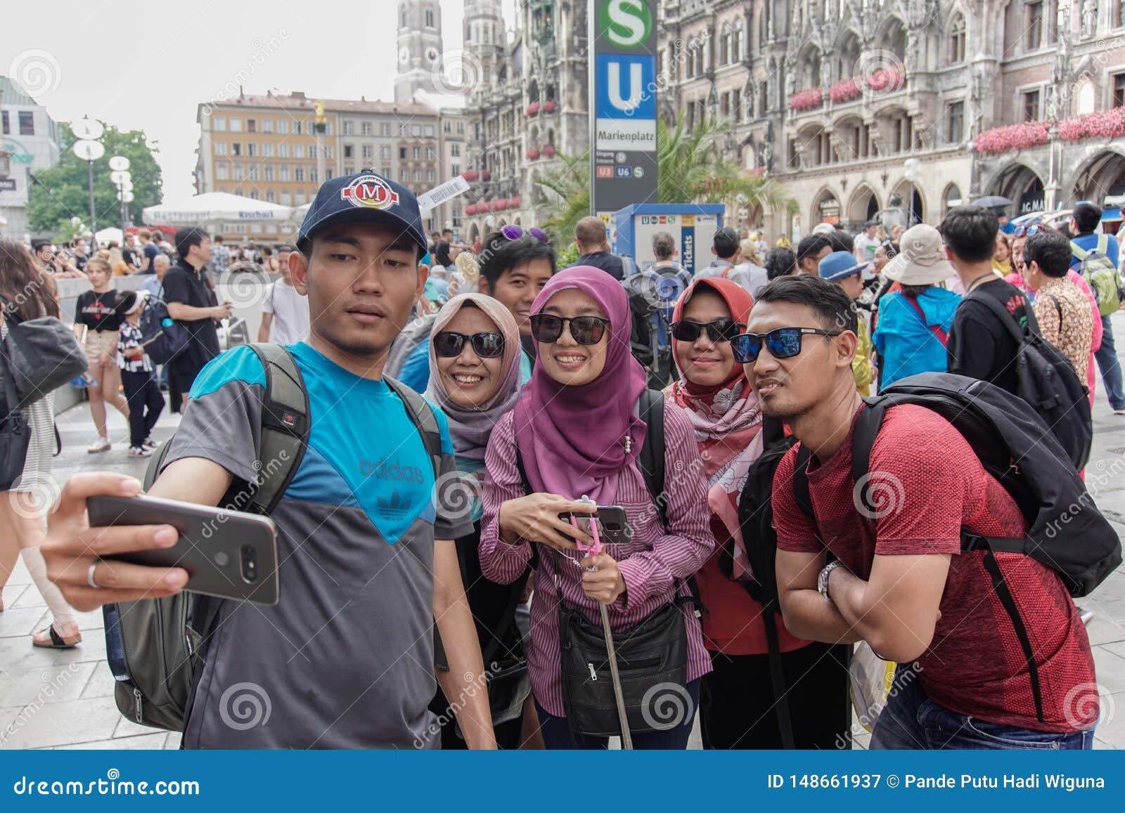 El turista musulmán asiático presenta en el peatón en Munich