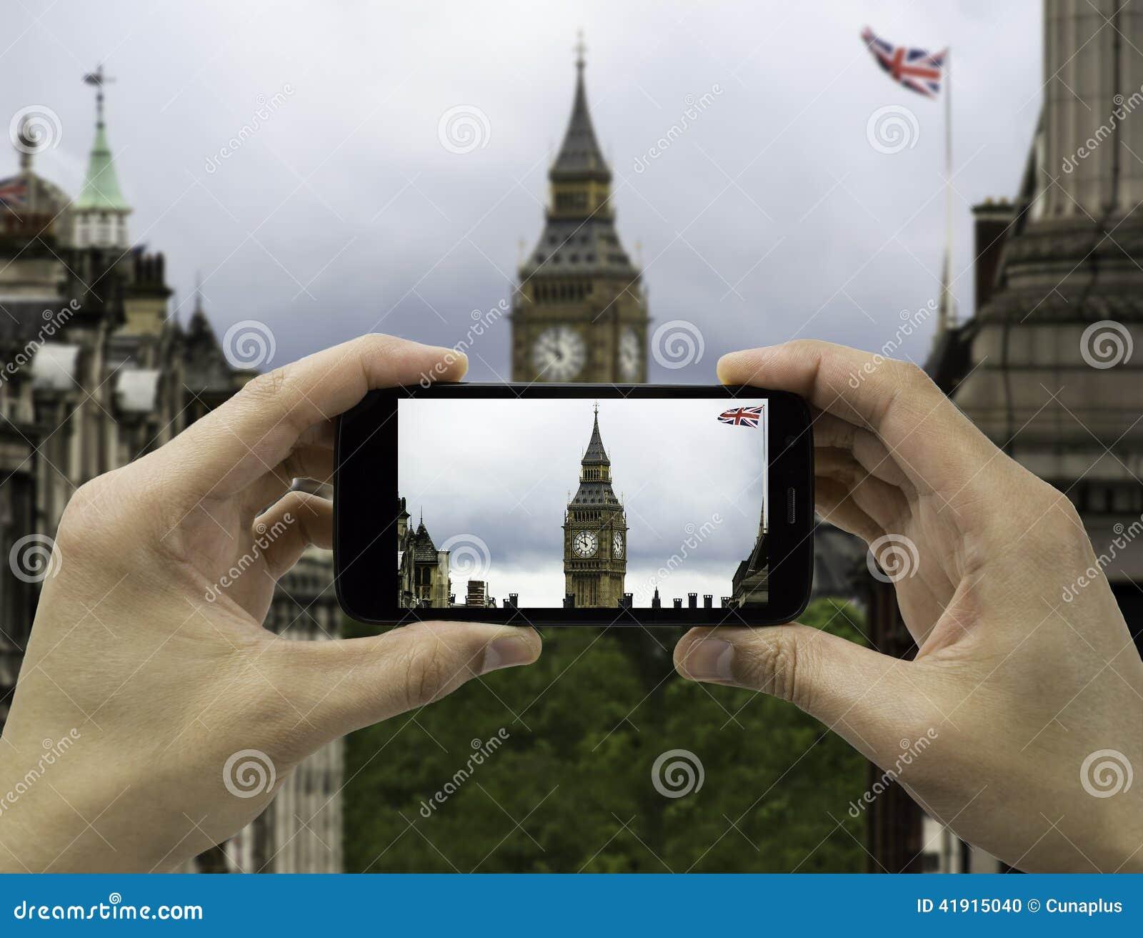 El turista soporta el móvil de la cámara en ben grande en bandera