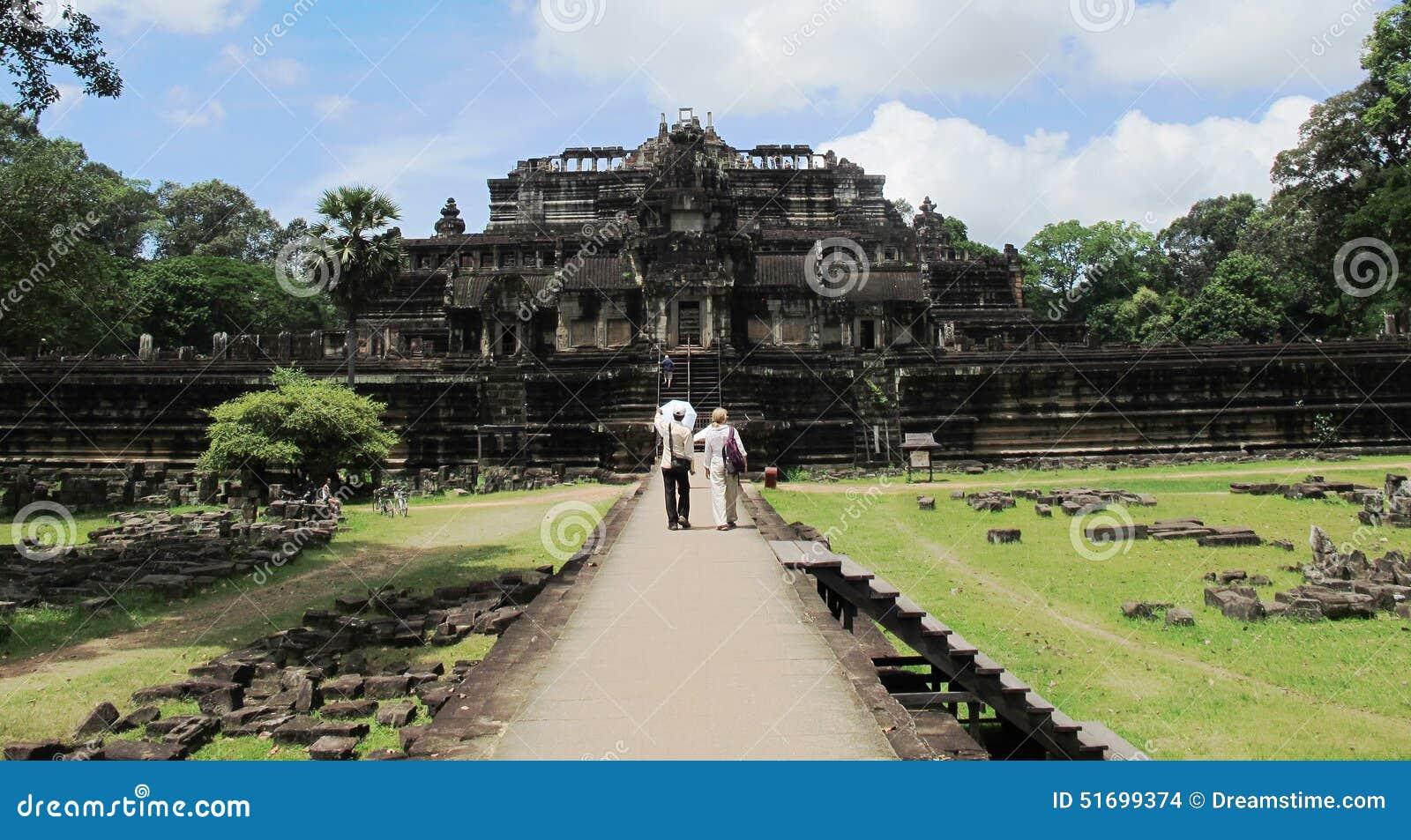 El turista y la guía caminan a un templo en el complejo de Angkor, Camboya