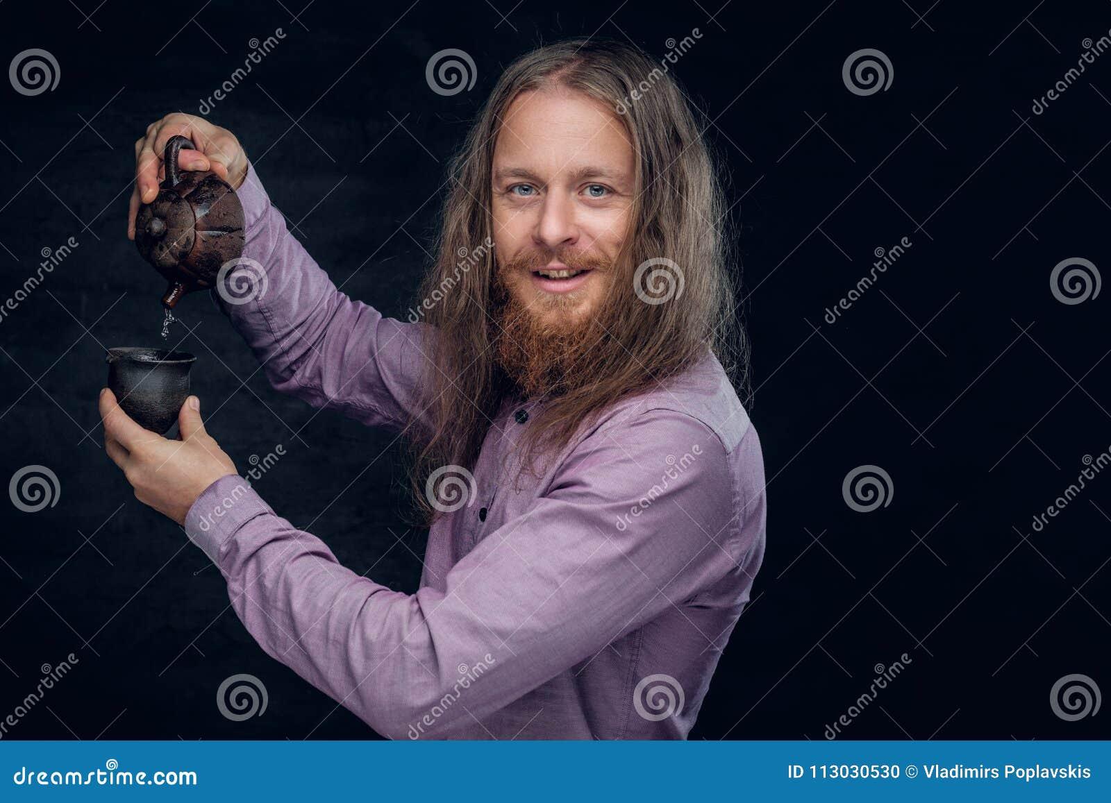 El varón barbudo con el pelo largo vierte té