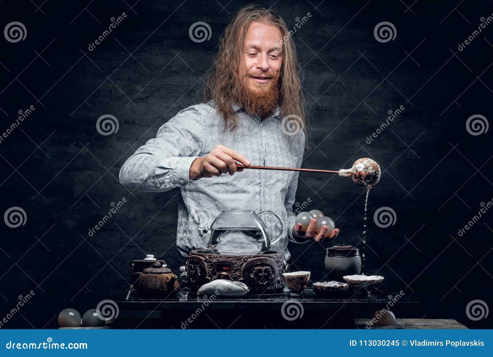 El varón barbudo positivo vierte té caliente