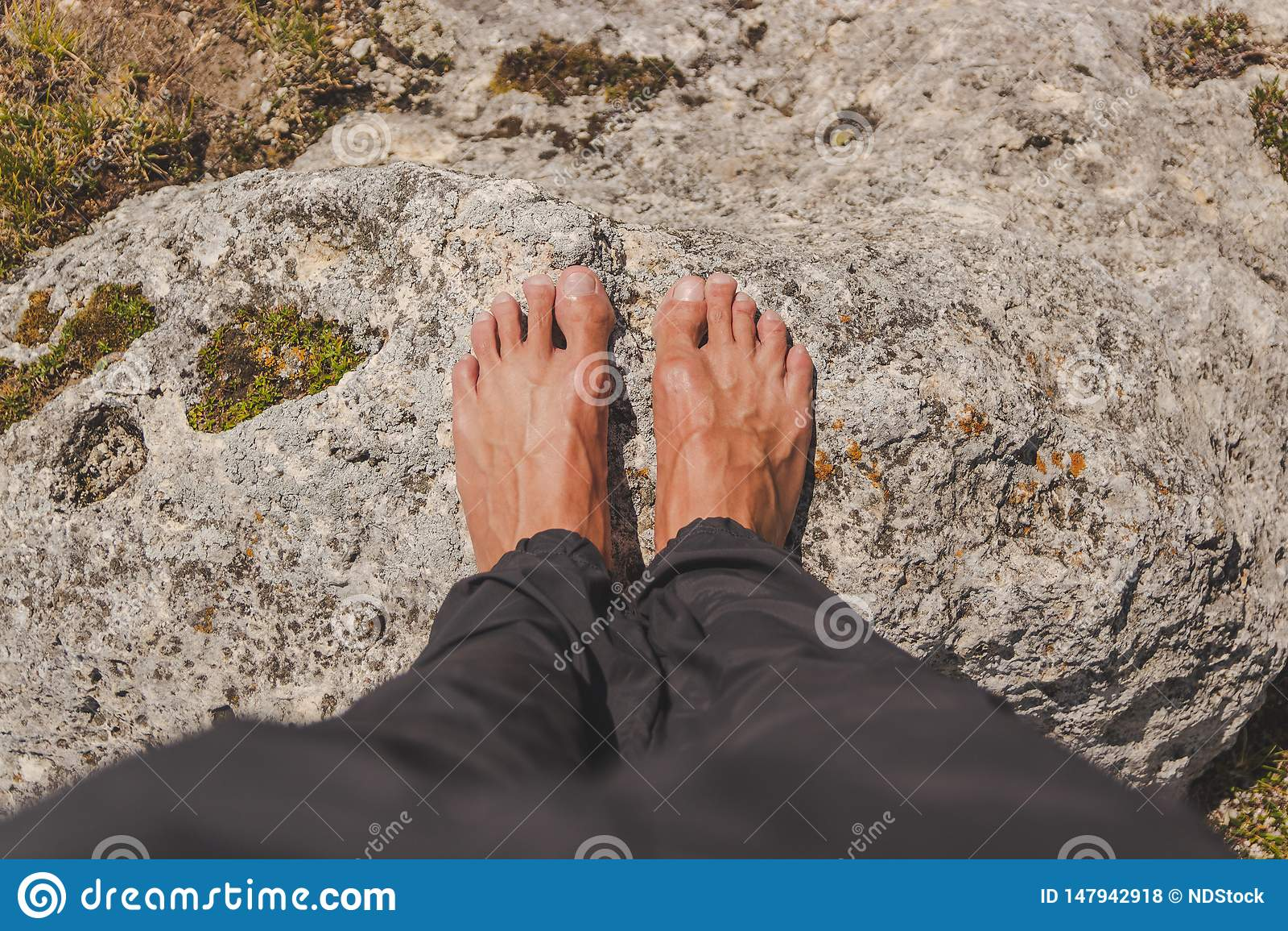 El varón colocó descalzo en una roca