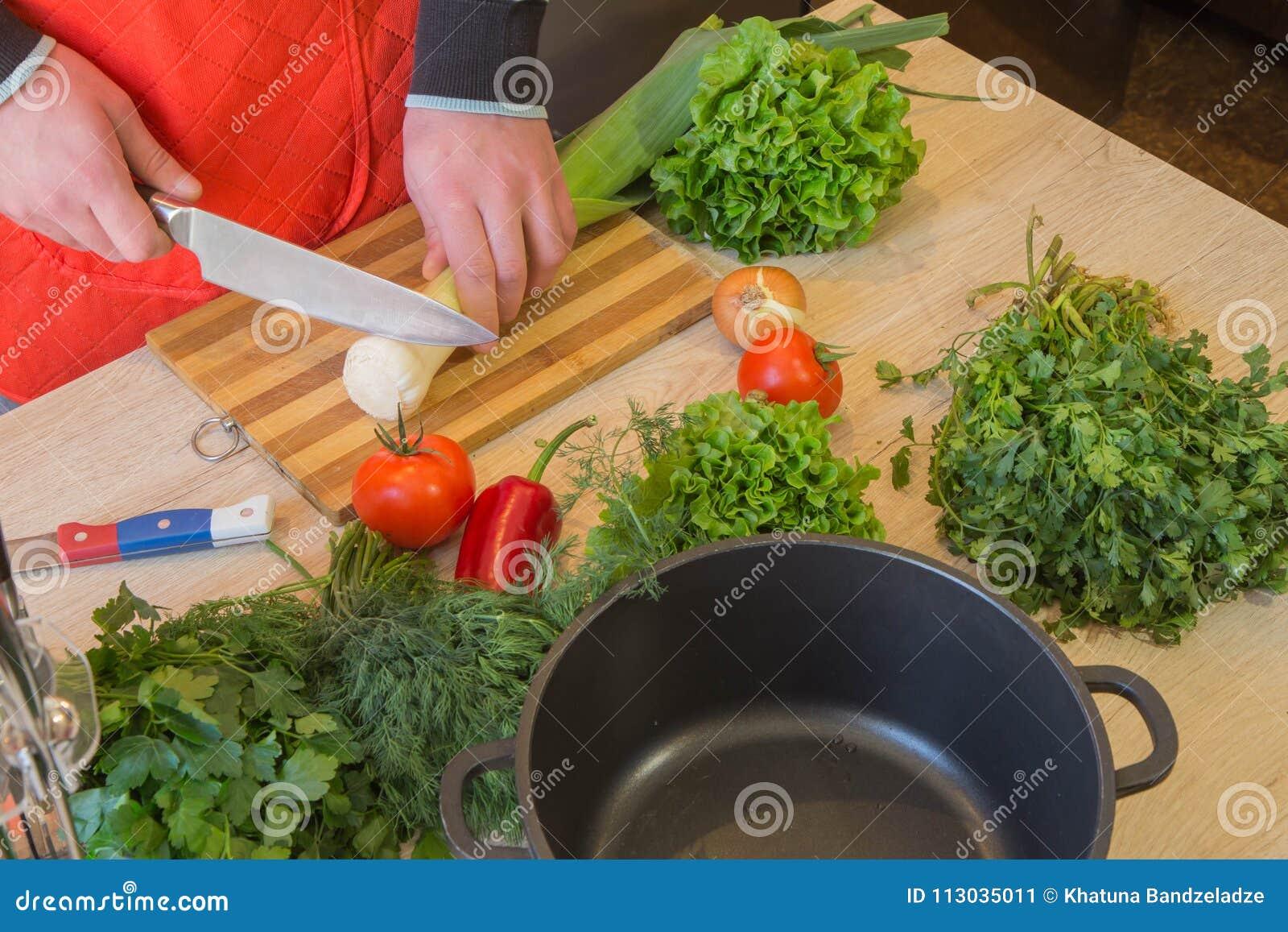 El varón da verduras del corte en la pizarra de la cocina Alimento sano Sirva la preparación de las verduras, cocinando la comida