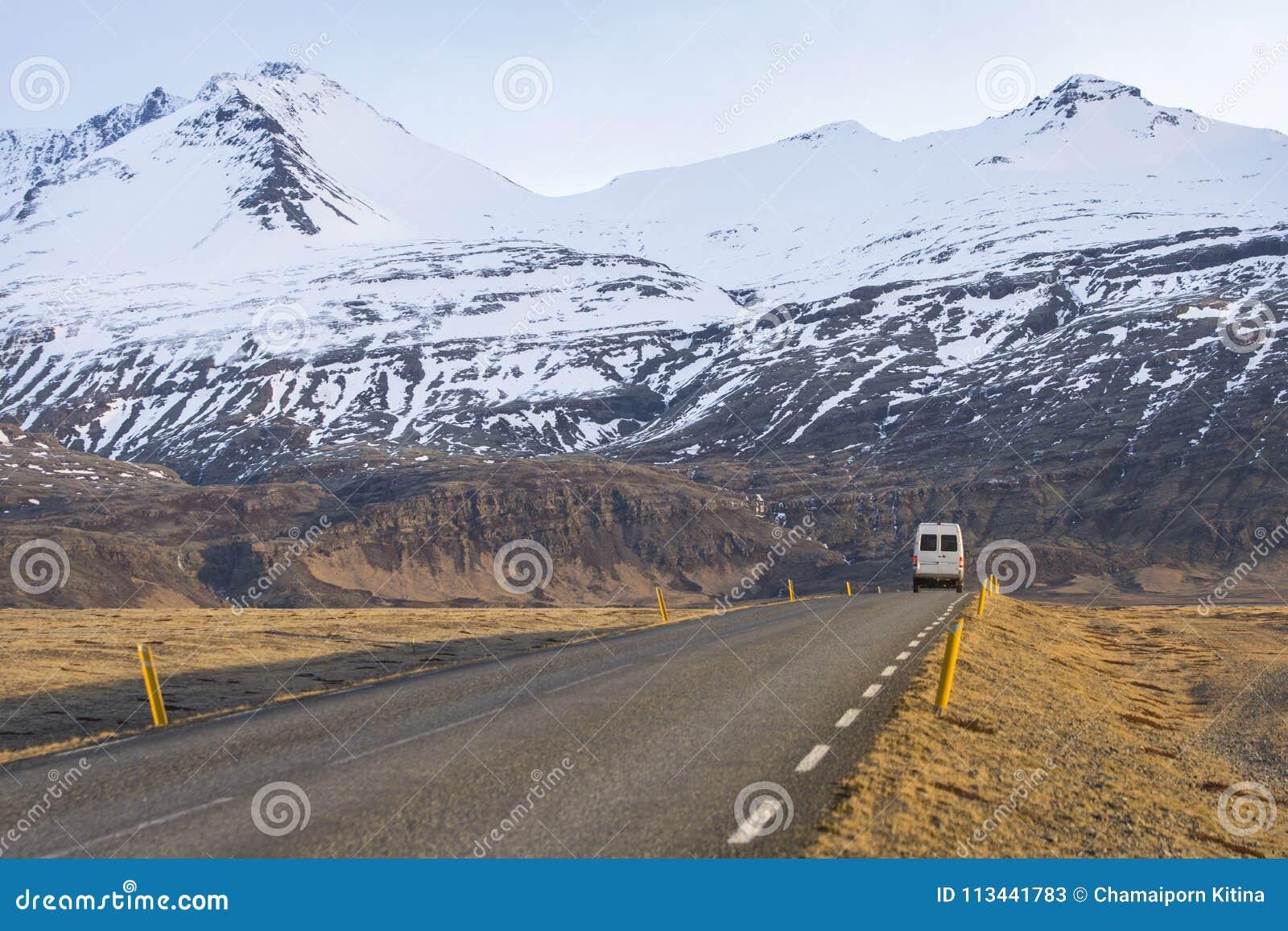 El vehículo recreativo en el camino islandés con nieve capsuló la montaña