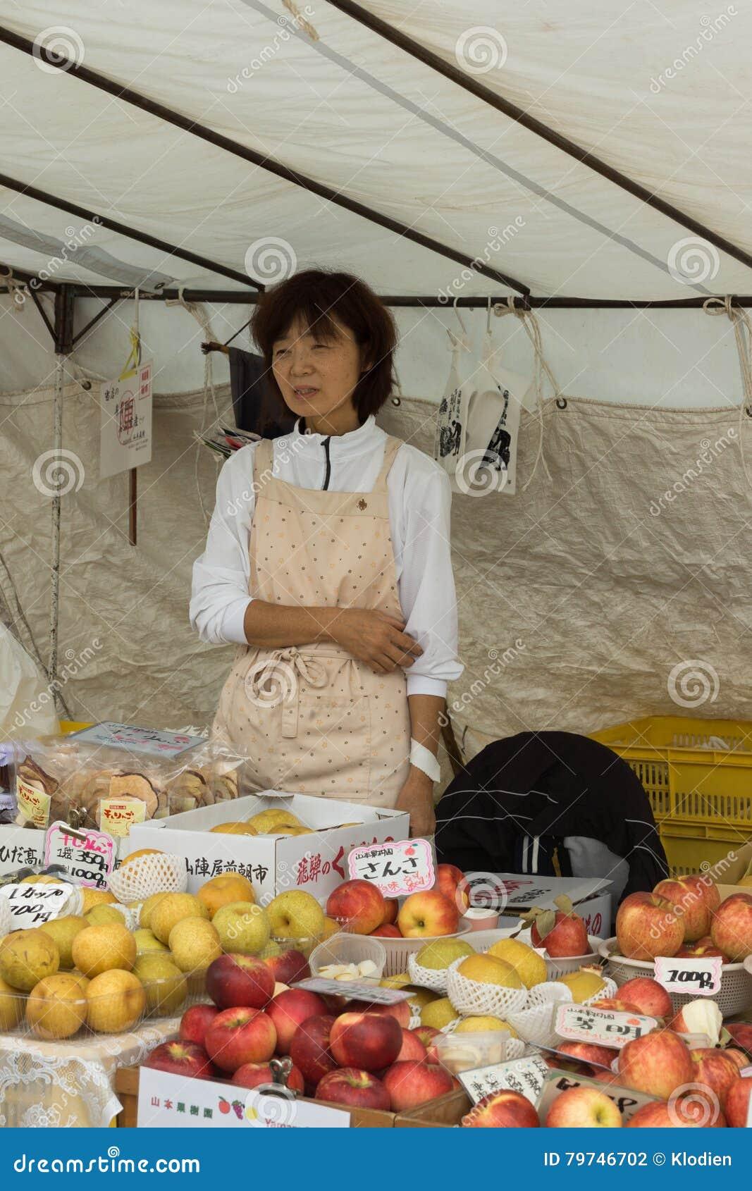 El vendedor de sexo femenino japonés envejecido centro vende manzanas