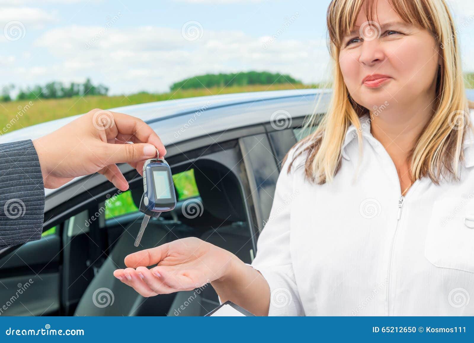El vendedor presenta la llave de la mujer del nuevo coche