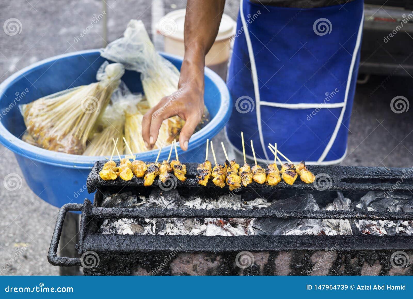 El vendedor satay que viajaba asó a la parrilla satay en el mercado de la noche
