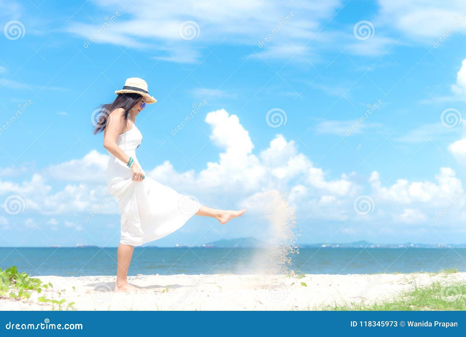 El verano blanco sonriente de la moda de la mujer que lleva asiática que camina en el océano arenoso vara La mujer disfruta y rel