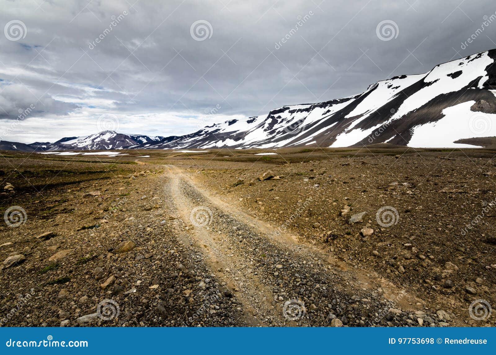 El viajar abajo de un camino de la grava en montañas nevosas de Islandia