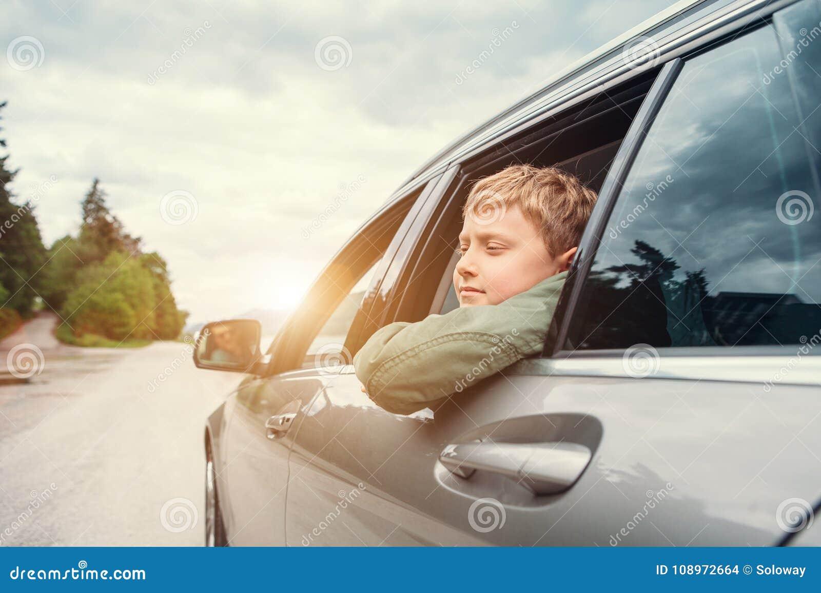 El viajar en auto - el hijo y el padre miran hacia fuera de las ventanillas del coche