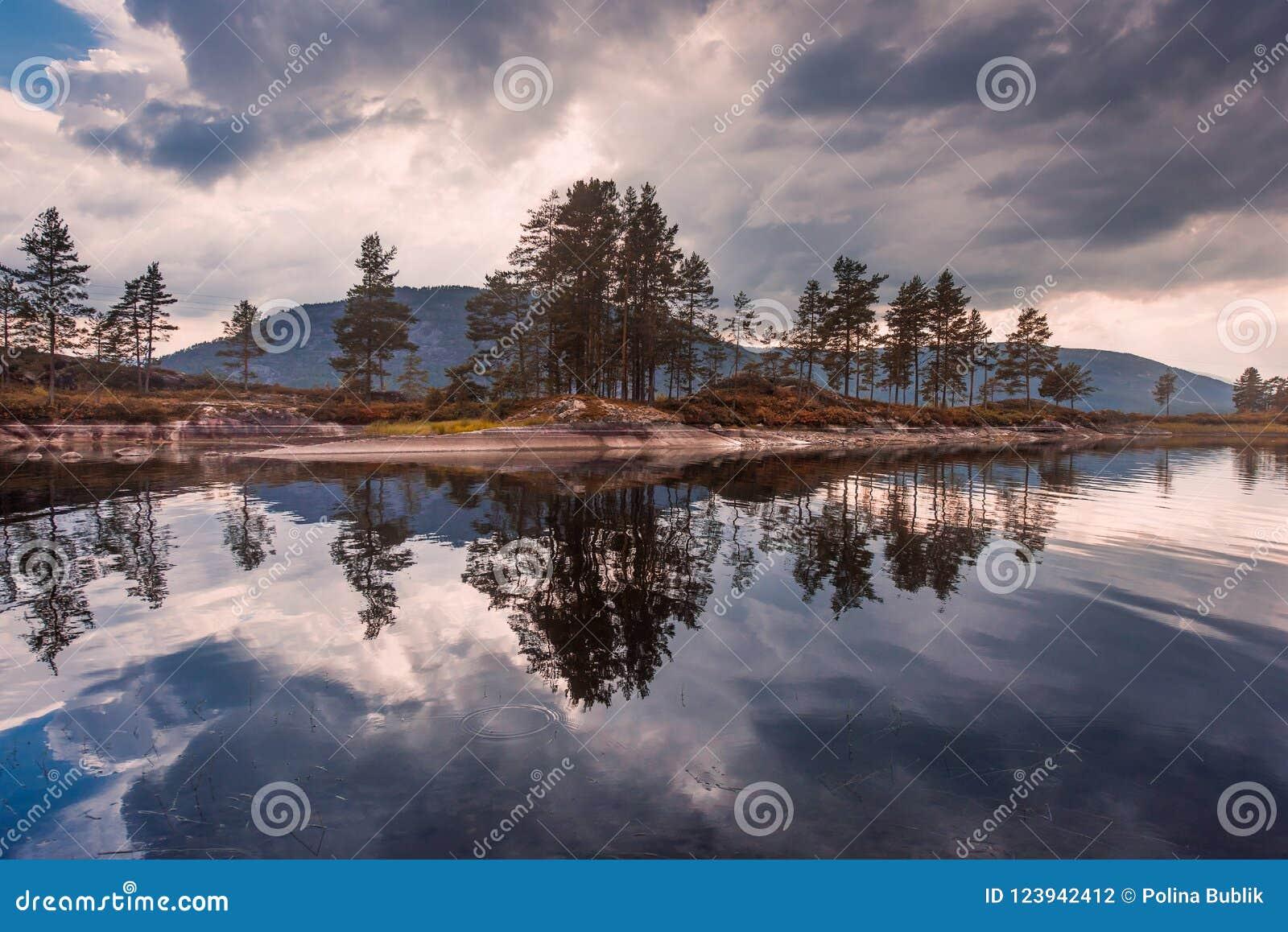 El viaje en la manera a la piedra del kjerag en las montañas kjeragbolten de Noruega, reflexión de árboles en el lago en los sole