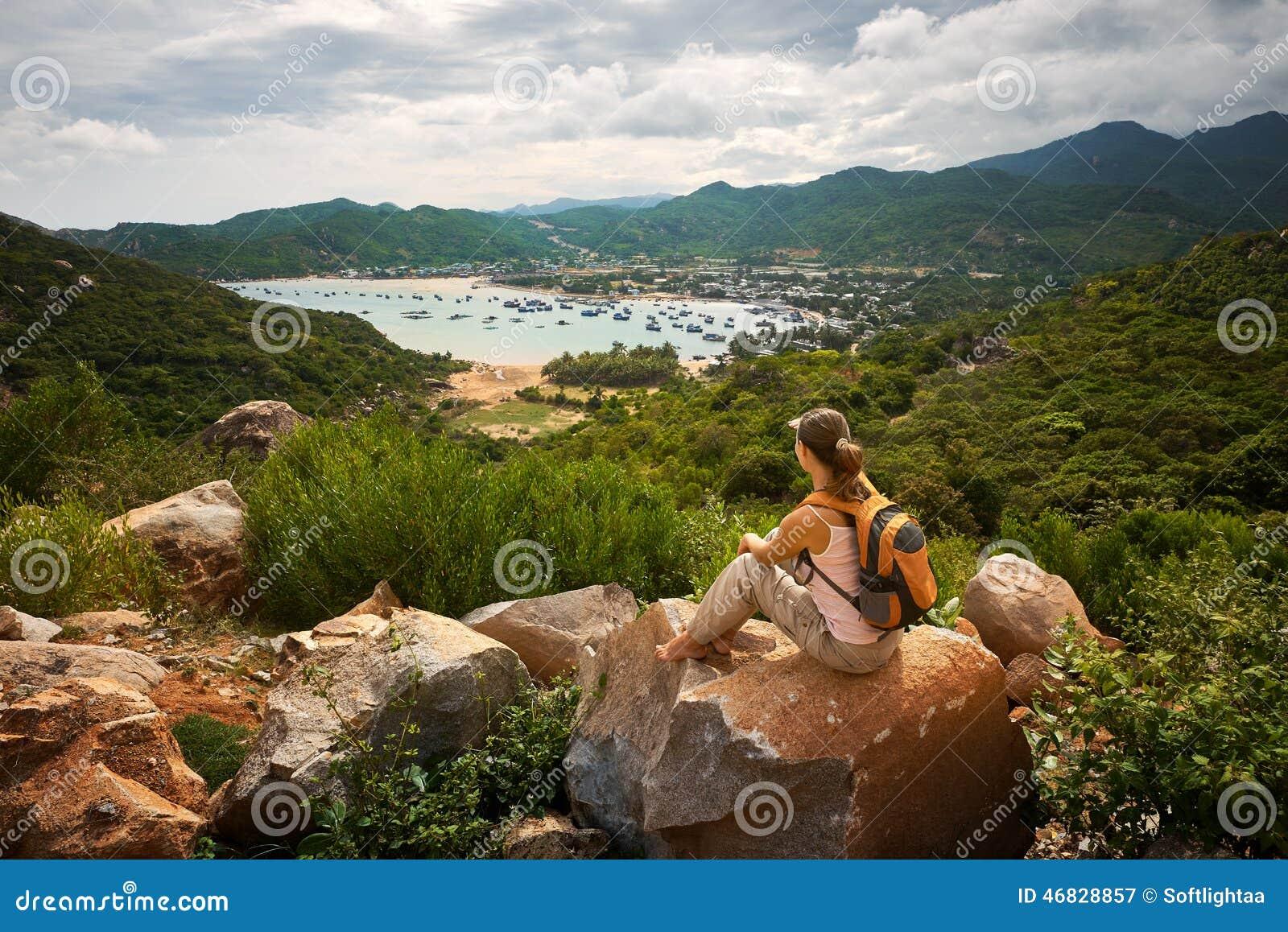 El viajero de la mujer mira el borde del acantilado en la bahía del mar del mounta