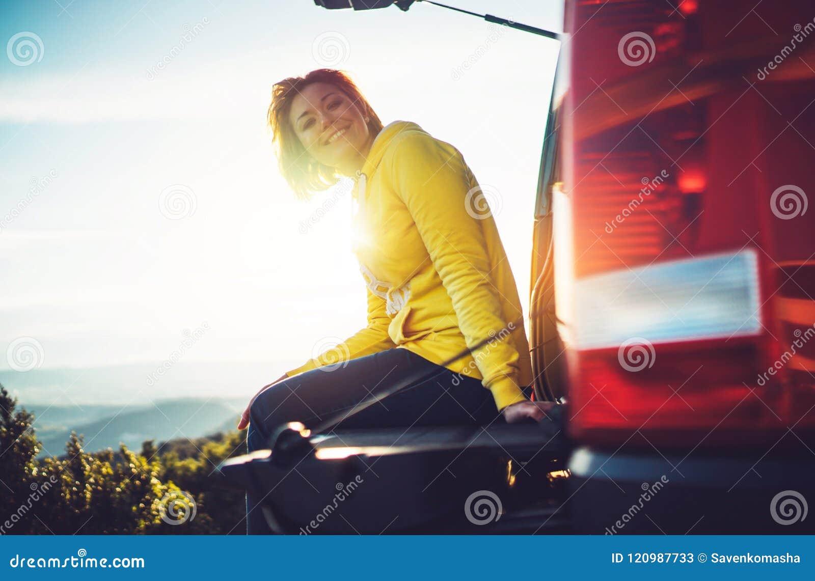 El viajero turístico que viaja en coche en el top del verde en la montaña, chica joven sonríe feliz contra puesta del sol del fon