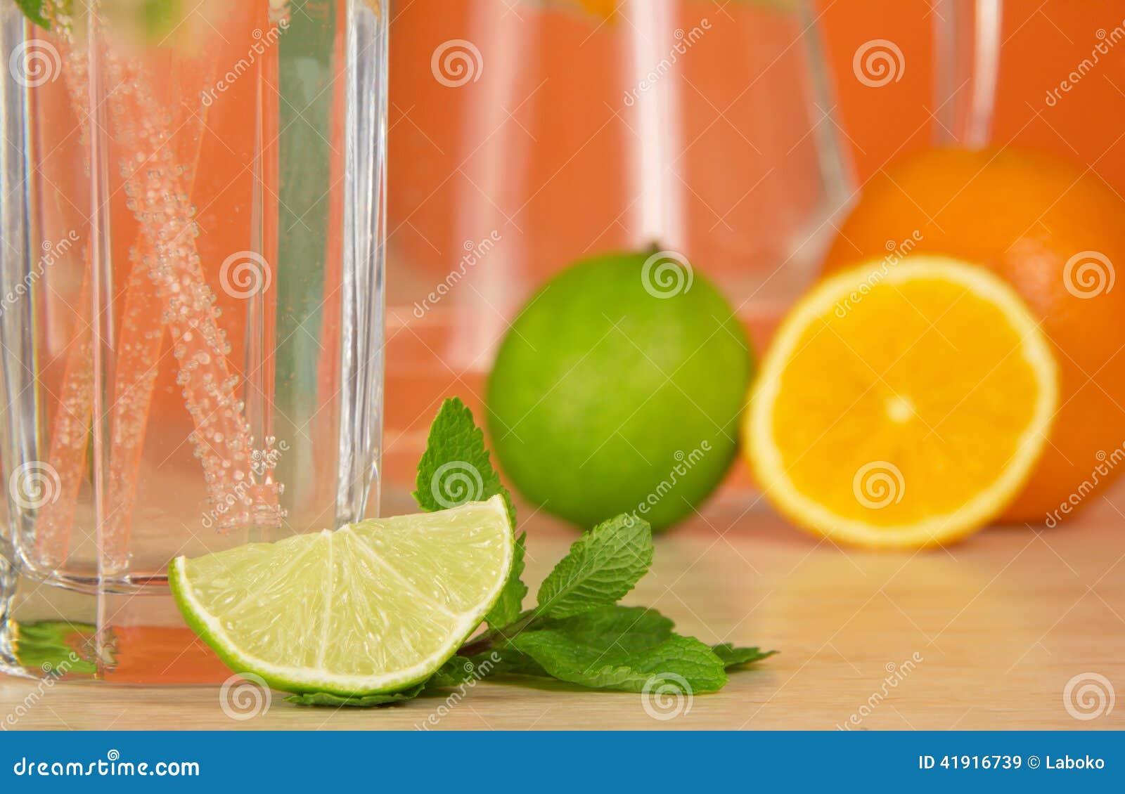 El vidrio con la bebida, la fruta cítrica y la menta verde hojean