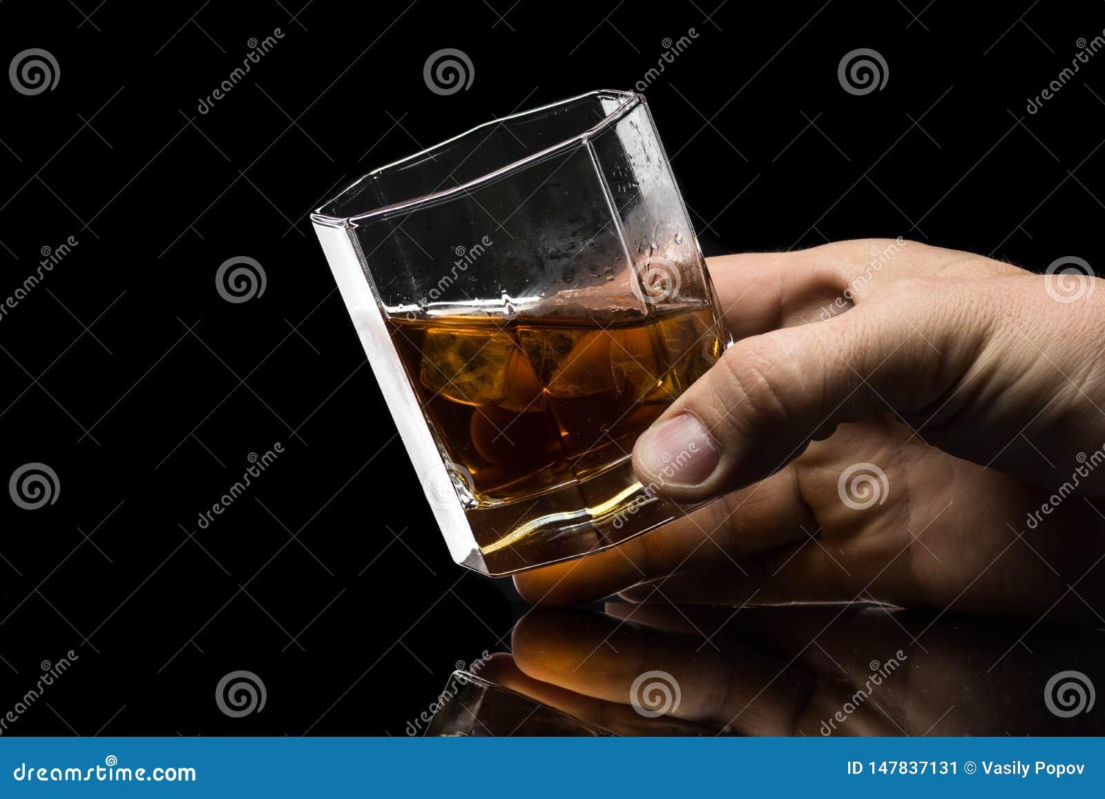 El vidrio hexagonal de brandy del whisky con hielo y salpica del hielo que cae