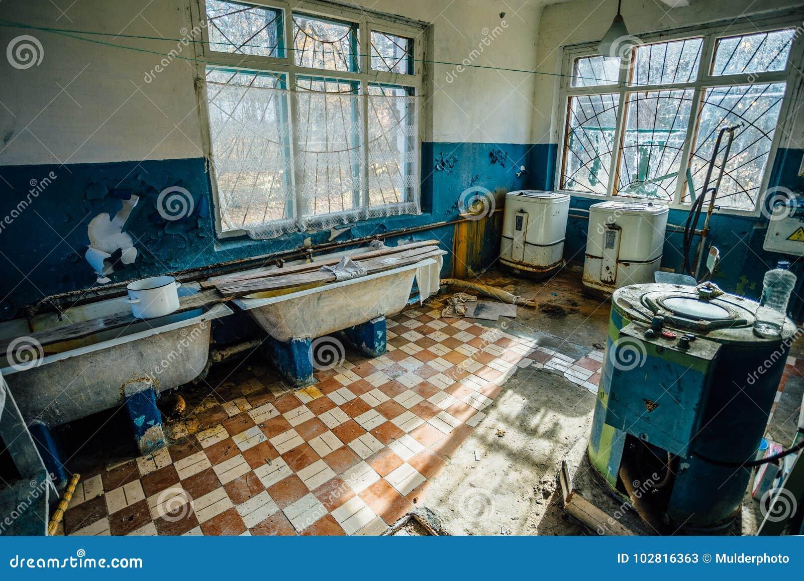 El viejo lavadero espeluznante con un piso sucio y máquinas rotas del lavado y se baña en un hospital psiquiátrico abandonado