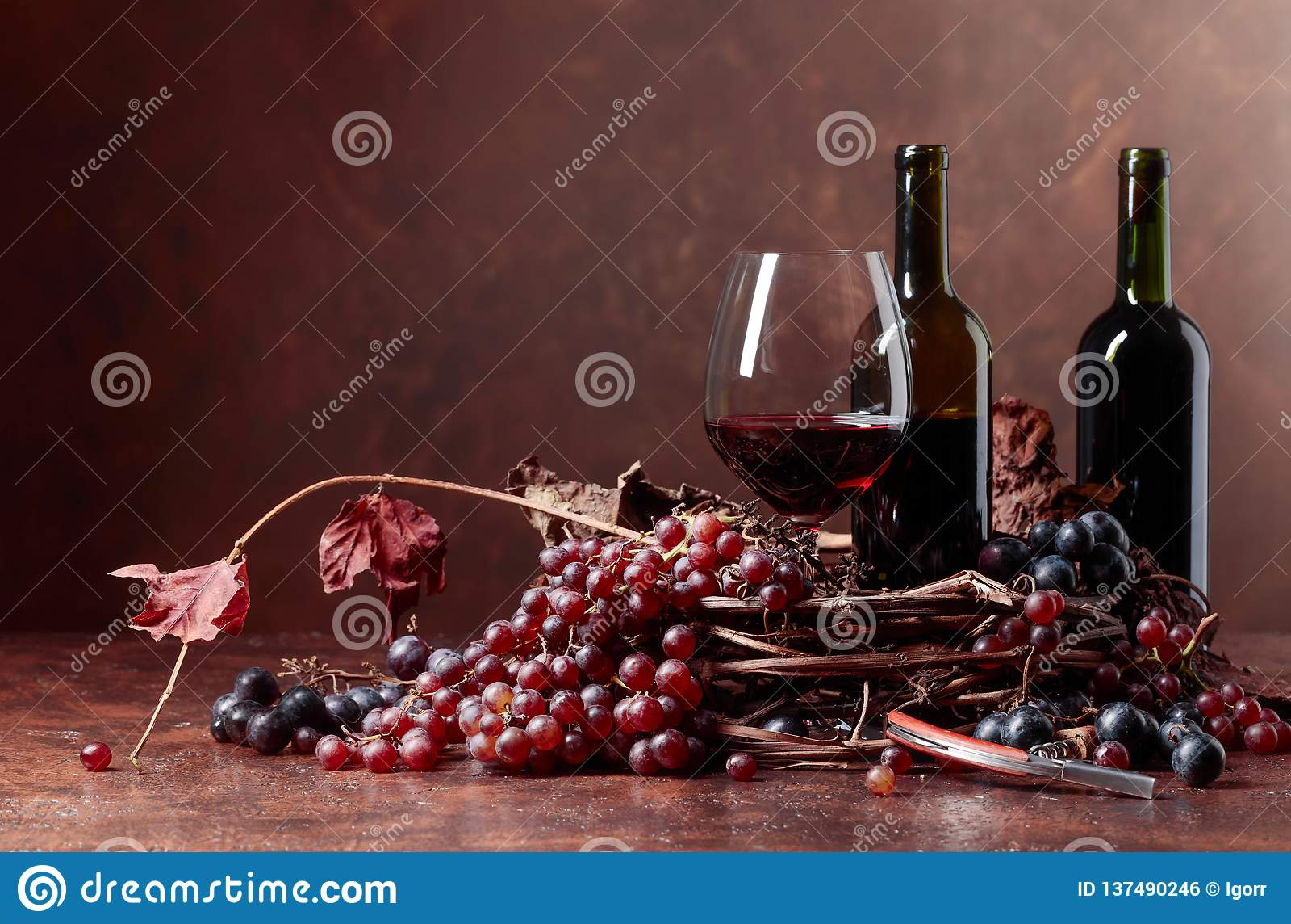 El vino rojo y las uvas frescas con secado encima de vid se va