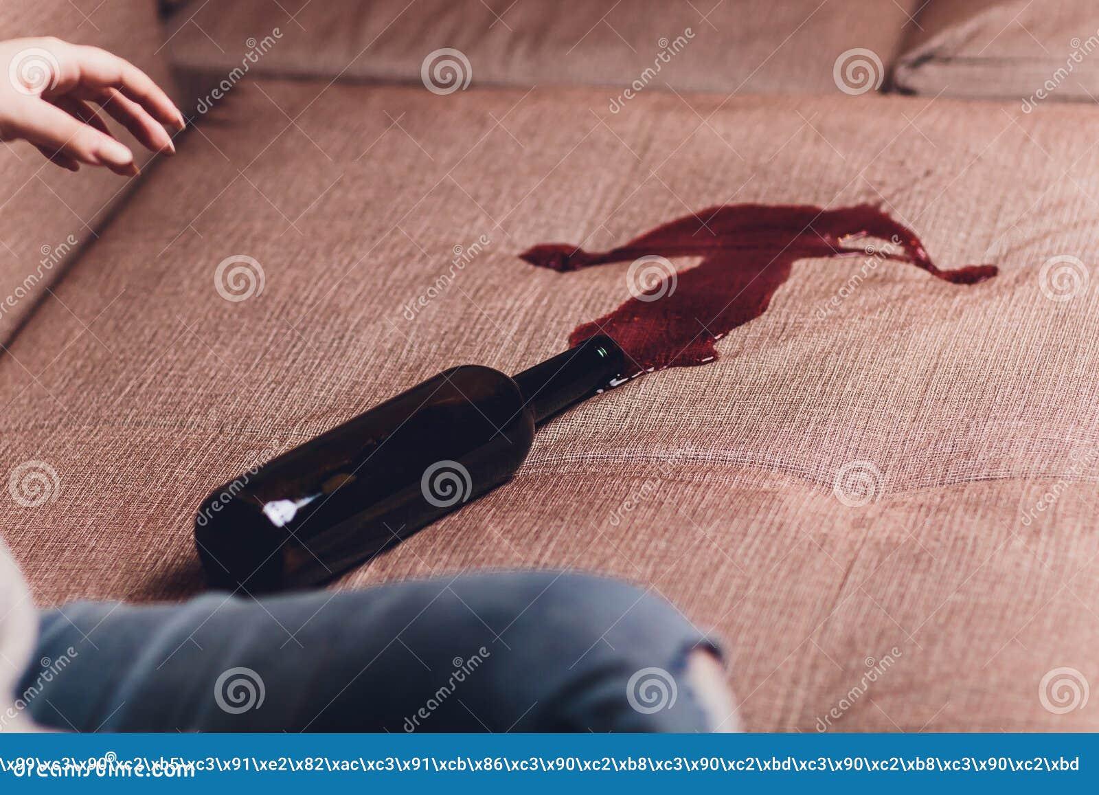 El vino tinto se derramó en un sofá marrón del sofá la botella oscura de vino tinto cayó