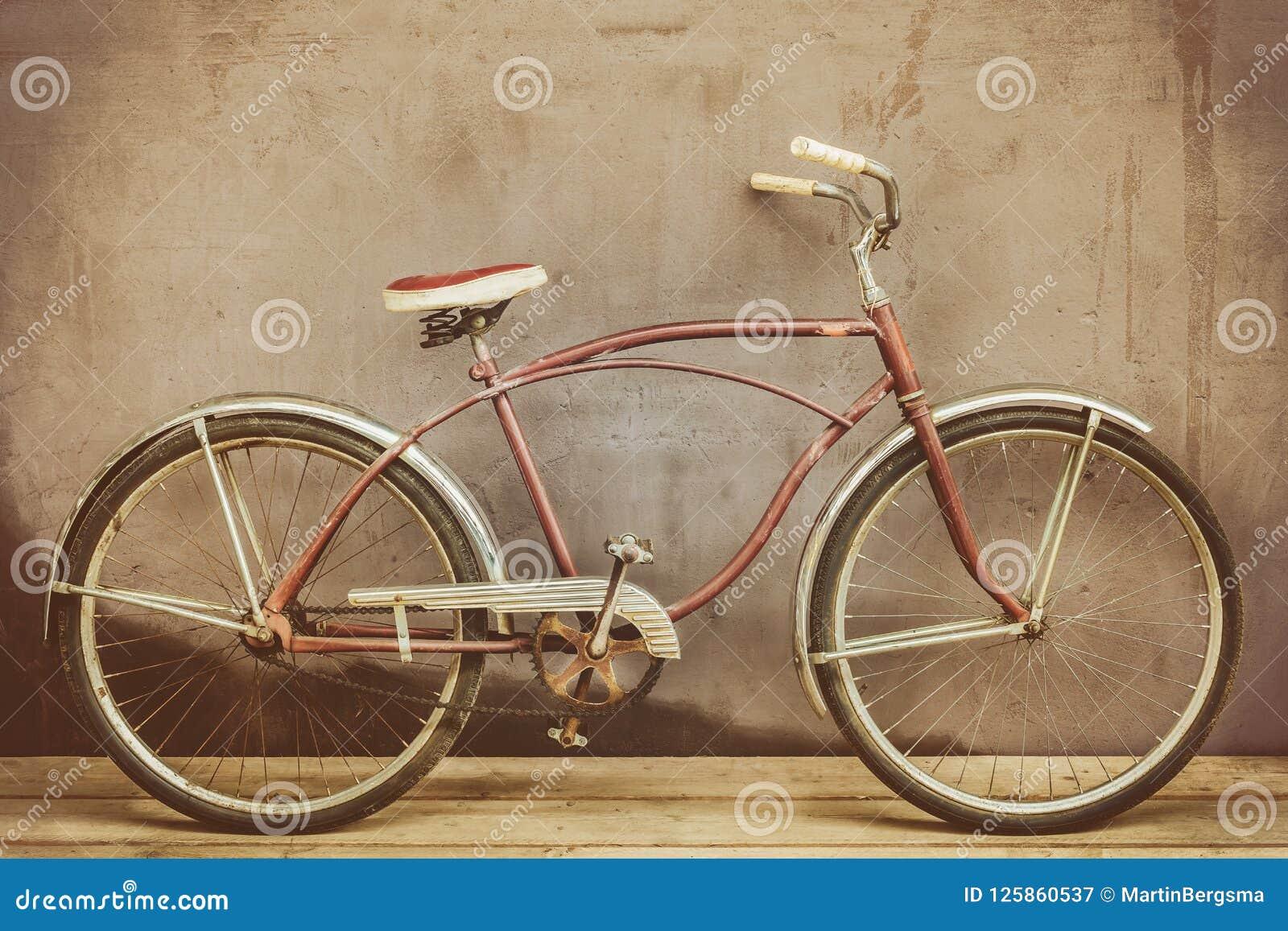 El vintage aherrumbró bicicleta del crucero en un piso de madera