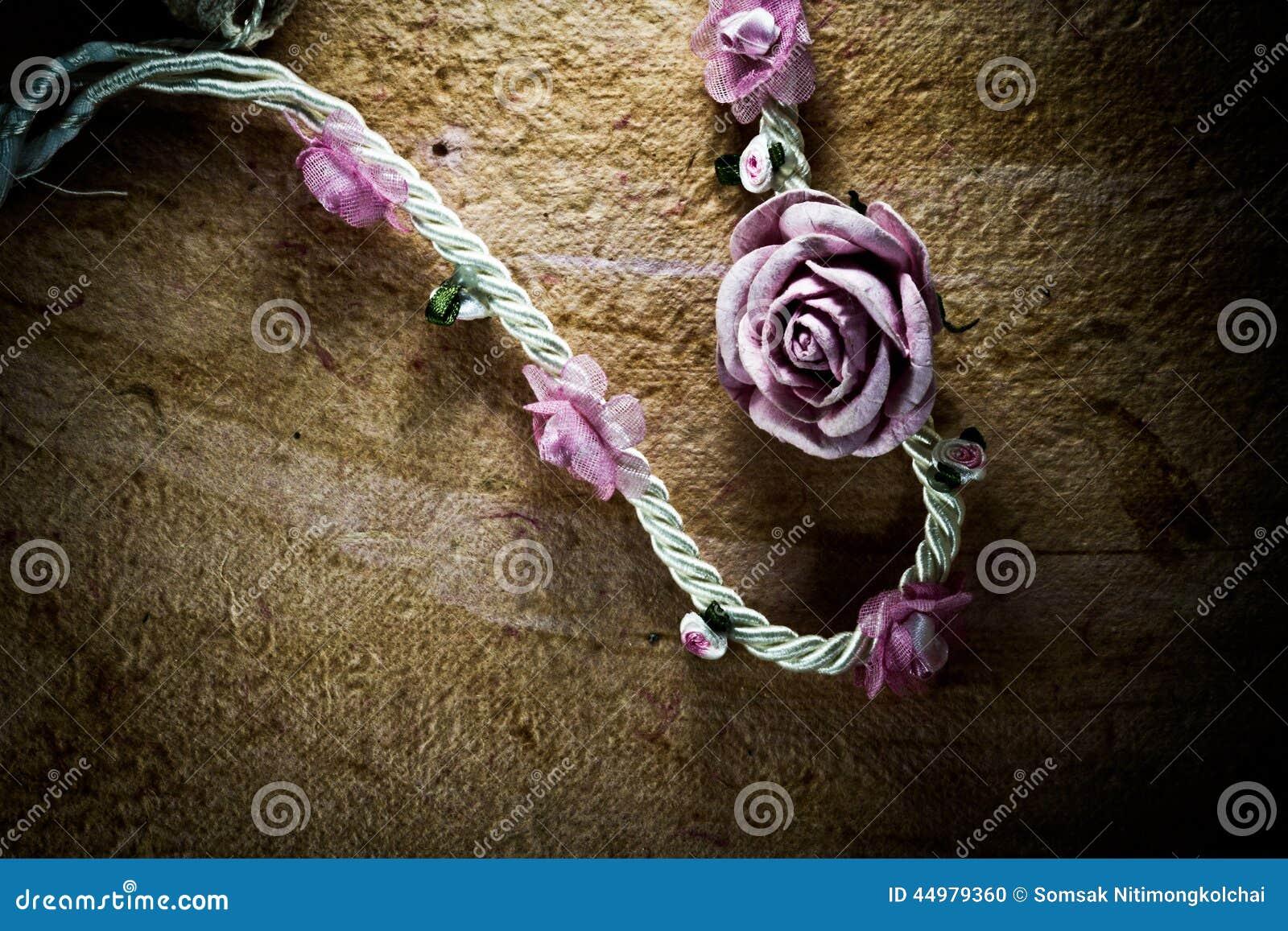 El vintage de flores artificiales subió en las rayas de papel viejas