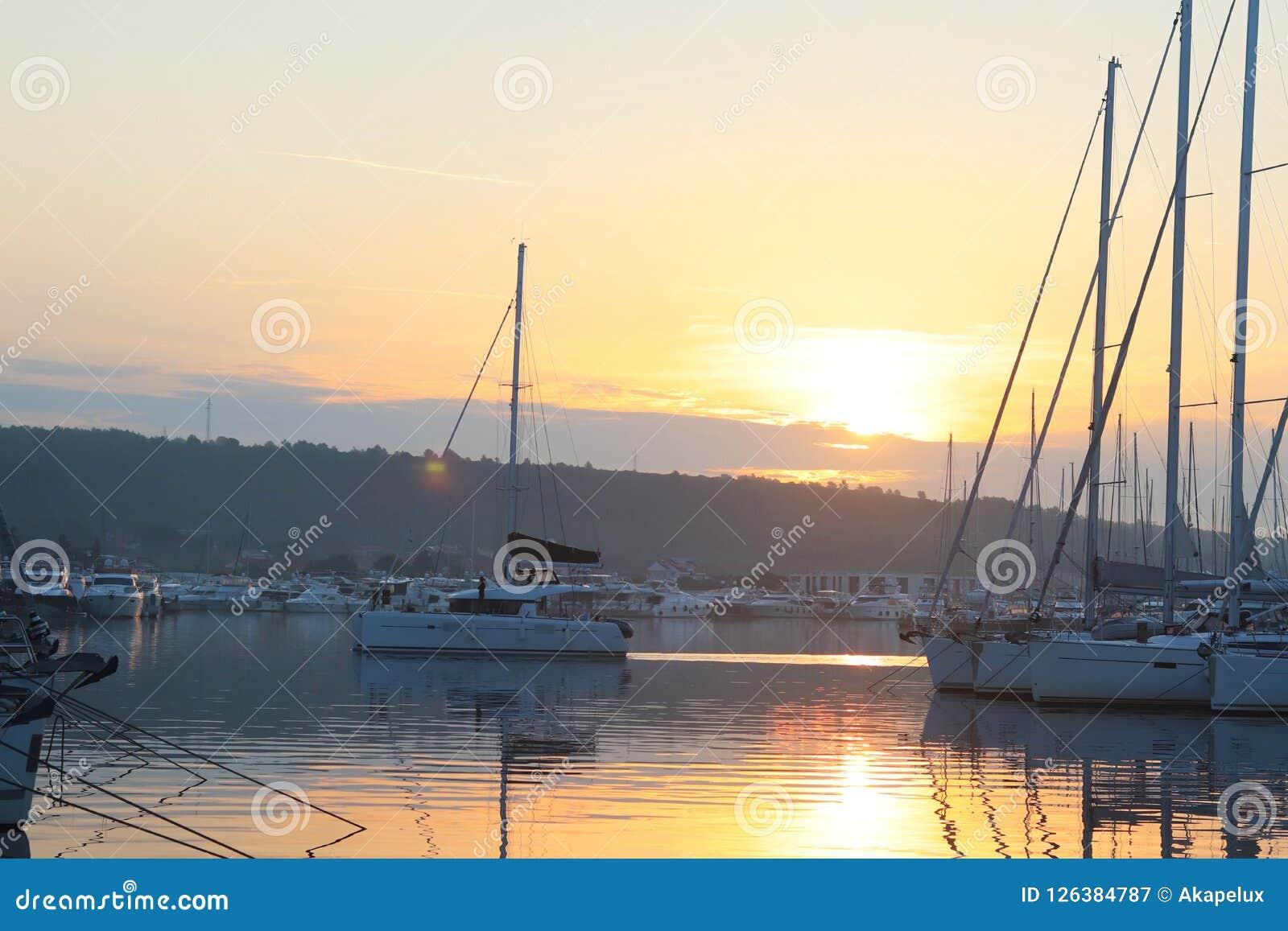 El yate vuelve del viaje al puerto deportivo durante el pasado de la navegación del amanecer de la mañana que la navegación amarr