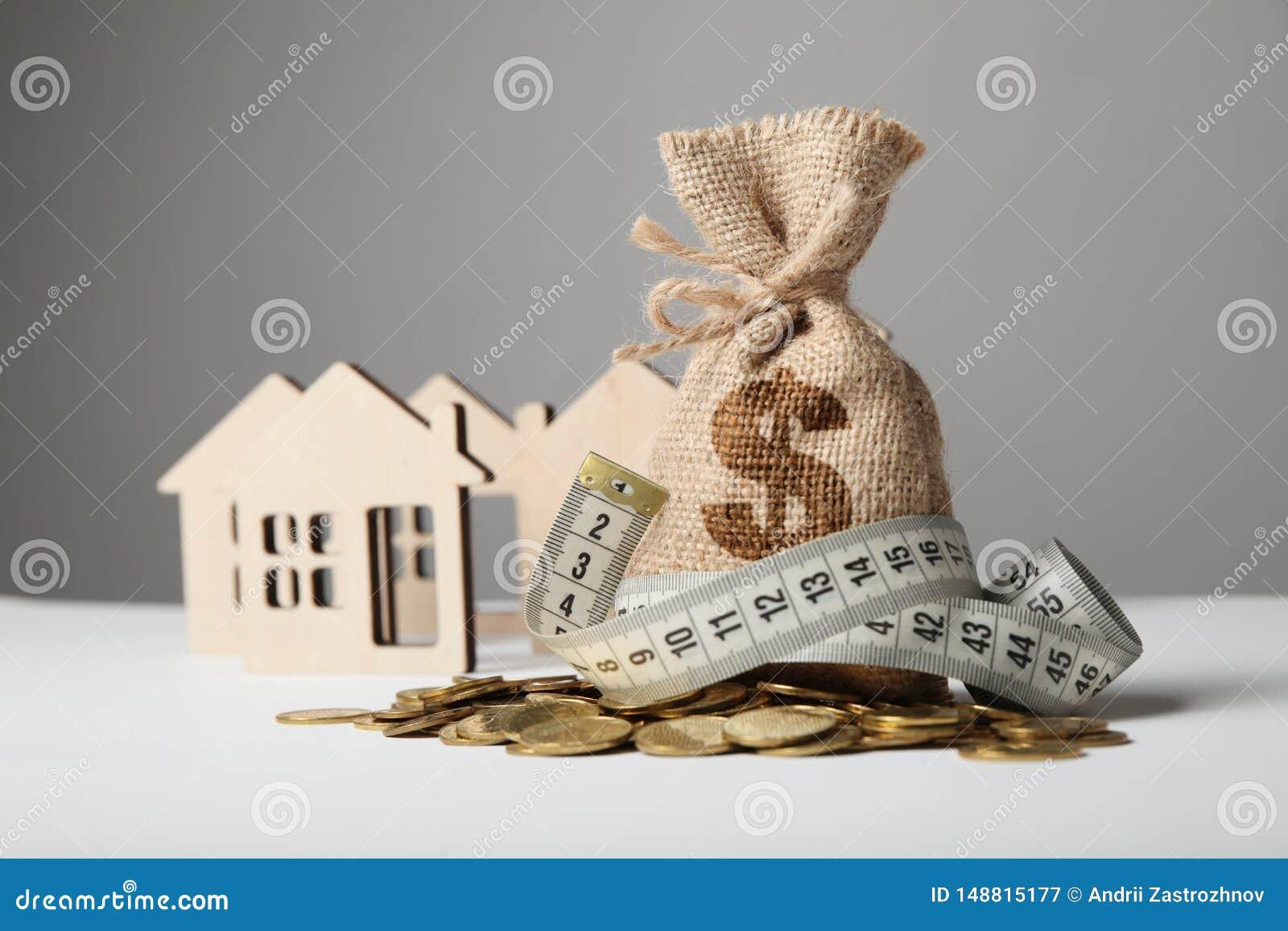 Elaborazione della borsa con il logo del dollaro sulle monete gialle e misurare nastro su fondo della figura della casa Oncept de