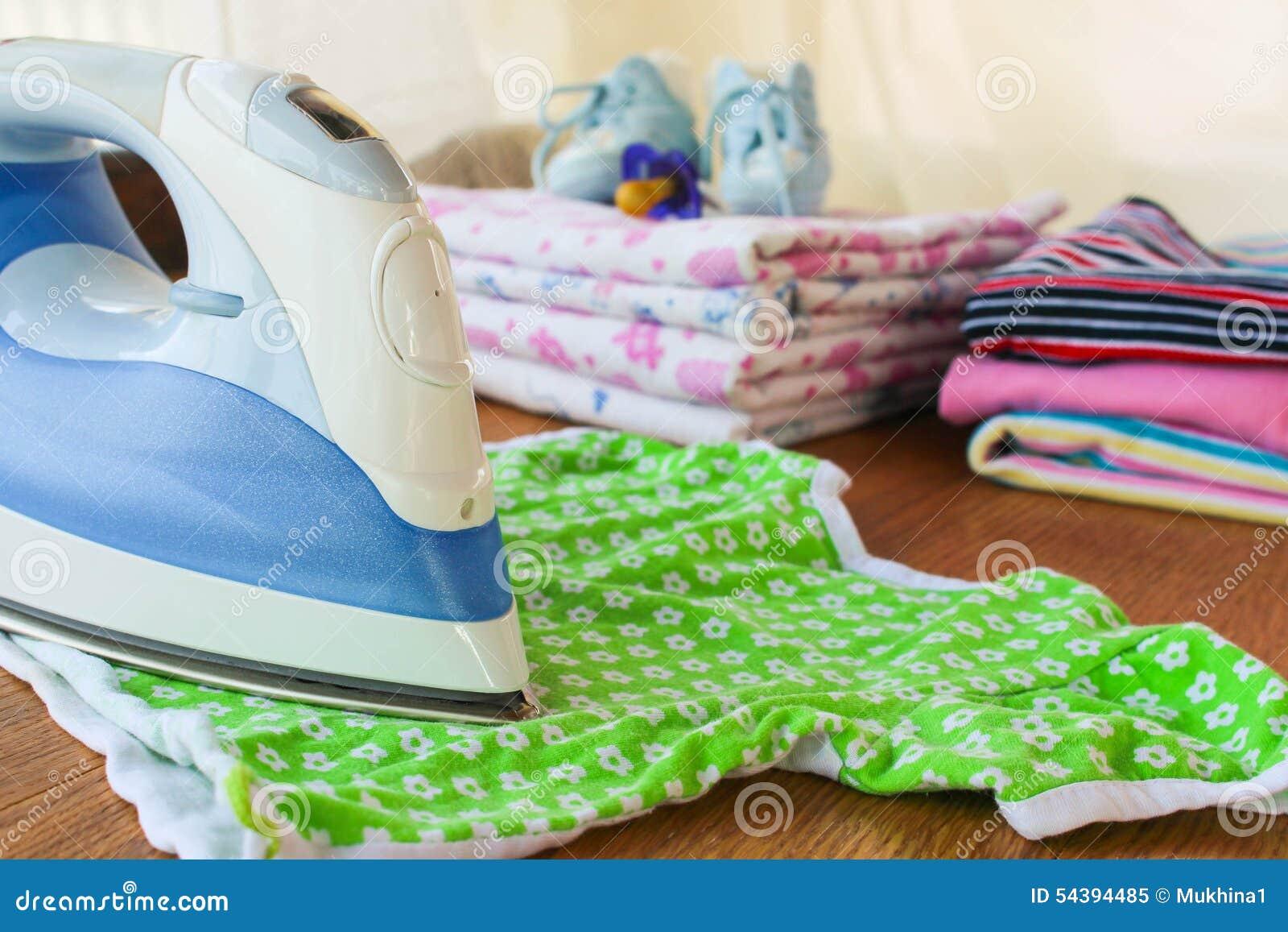 Żelazo muska children koszulkę W tle, pieluszki, dziecko odziewają, pacyfikator, mali buty i butelka mleko,