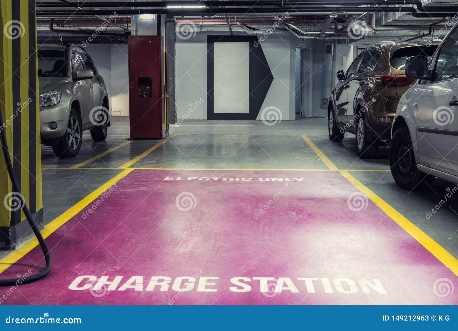 Elbiluppladdningsstation i underjordisk inomhus parkering av gallerian eller kontorsbyggnad Reserverad parkeringsplats f?r milj?